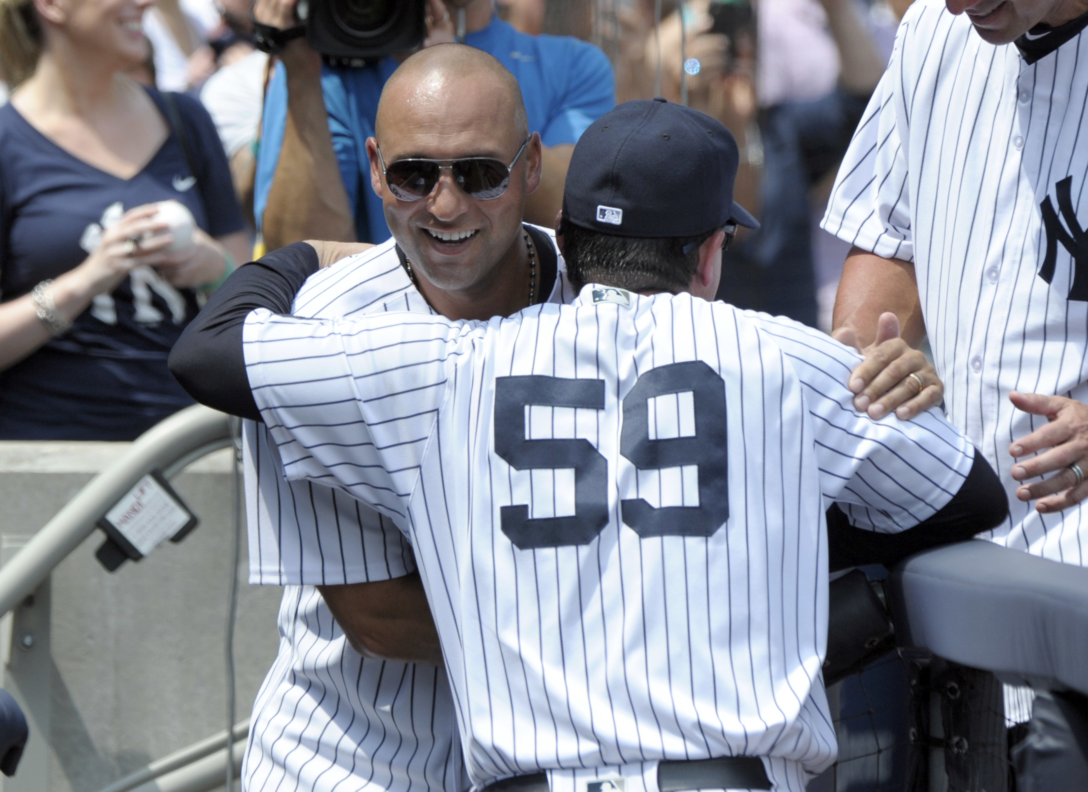Former New York Yankees shortstop Derek Jeter hugs bench coach Rob Thompson before a baseball game against the Tampa Bay Rays Saturday, Aug.13, 2016, at Yankee Stadium in New York. The 1996 Yankees team was honored before the game. (AP Photo/Bill Kostroun