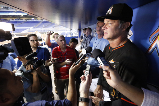 Miami Marlins manager Don Mattingly, right, talks to members of the media before the start of a baseball game against the Chicago White Sox, Saturday, Aug. 13, 2016, in Miami. Mattingly says Marlins officials haven't discussed trying to coax Alex Rodrigue