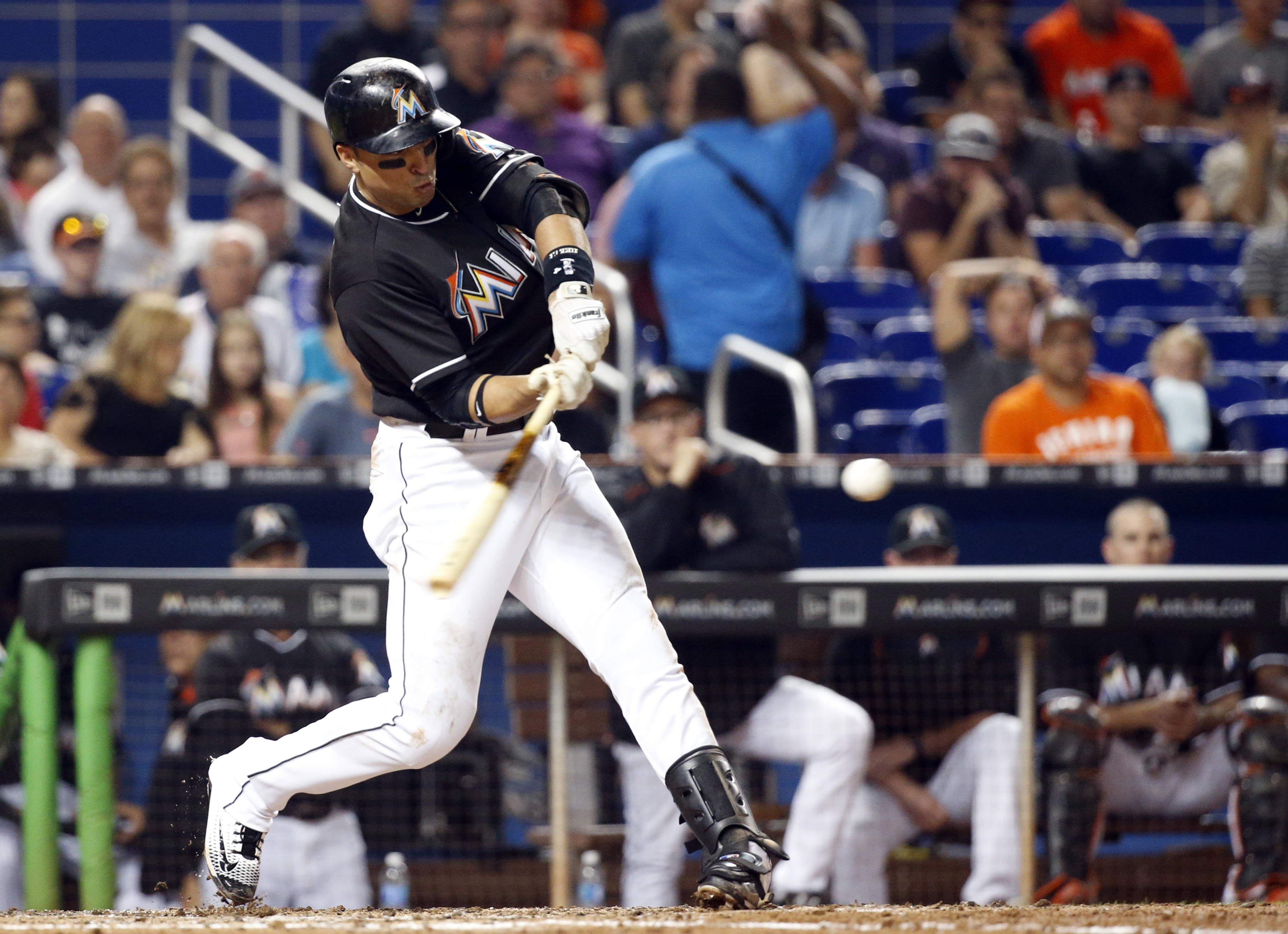 Miami Marlins' Martin Prado hits a home run, scoring Adam Conley and Dee Gordon, during the third inning of a baseball game against the Chicago White Sox, Saturday, Aug. 13, 2016, in Miami. (AP Photo/Wilfredo Lee)