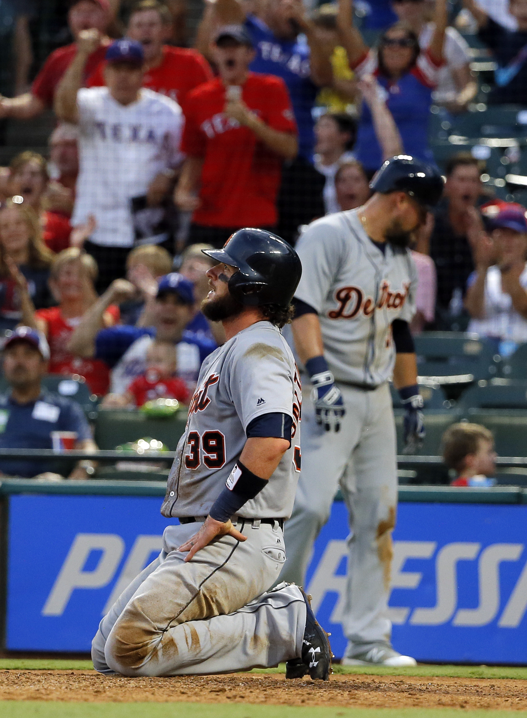 Detroit Tigers' Jarrod Saltalamacchia kneels by the plate moments after being tagged out by Texas Rangers' Jonathan Lucroy on a close play at the plate in the fourth inning of a baseball game, Saturday, Aug. 13, 2016, in Arlington, Texas. Saltalamacchia w