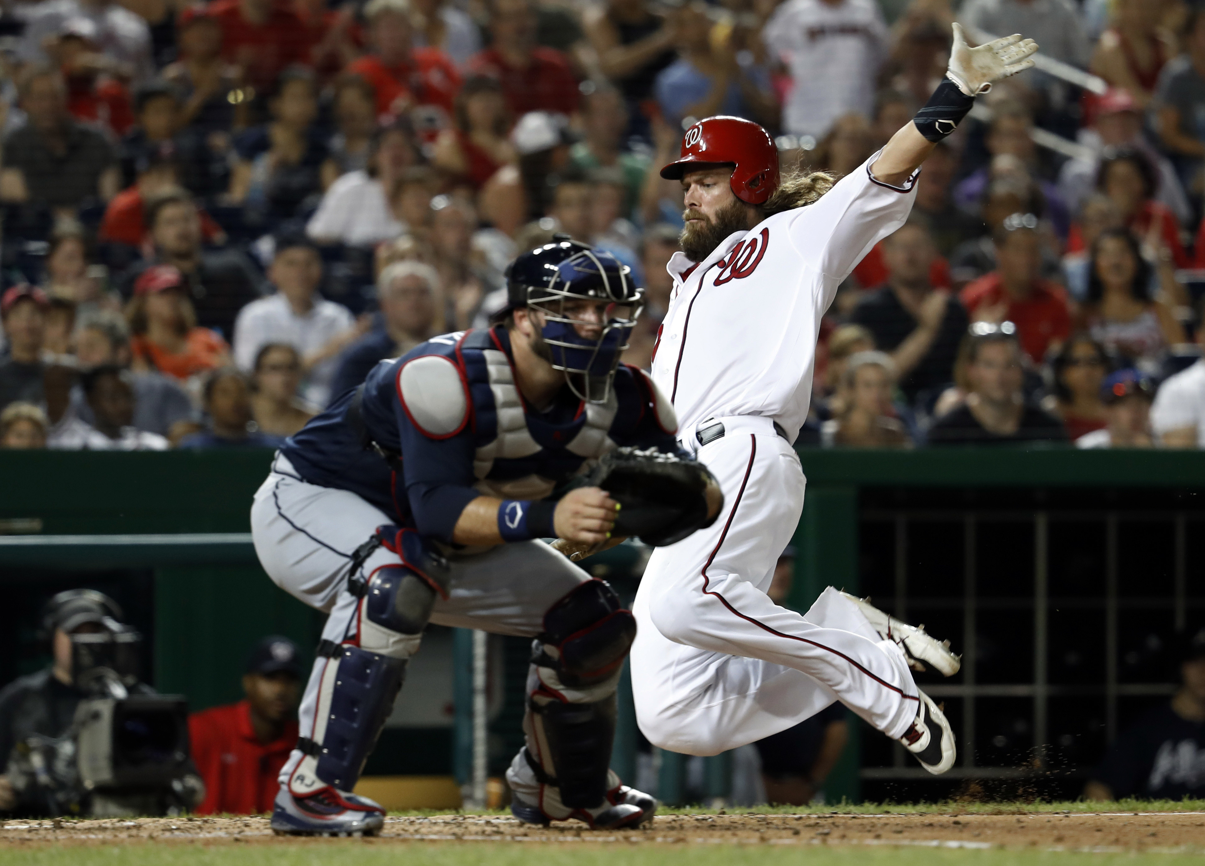 Washington Nationals' Jayson Werth, right, leaps to slide into home to score off a single hit by teammate Danny Espinosa as Atlanta Braves catcher A.J. Pierzynski, left, waits for the throw during the sixth inning of a baseball game at Nationals Park, Sat