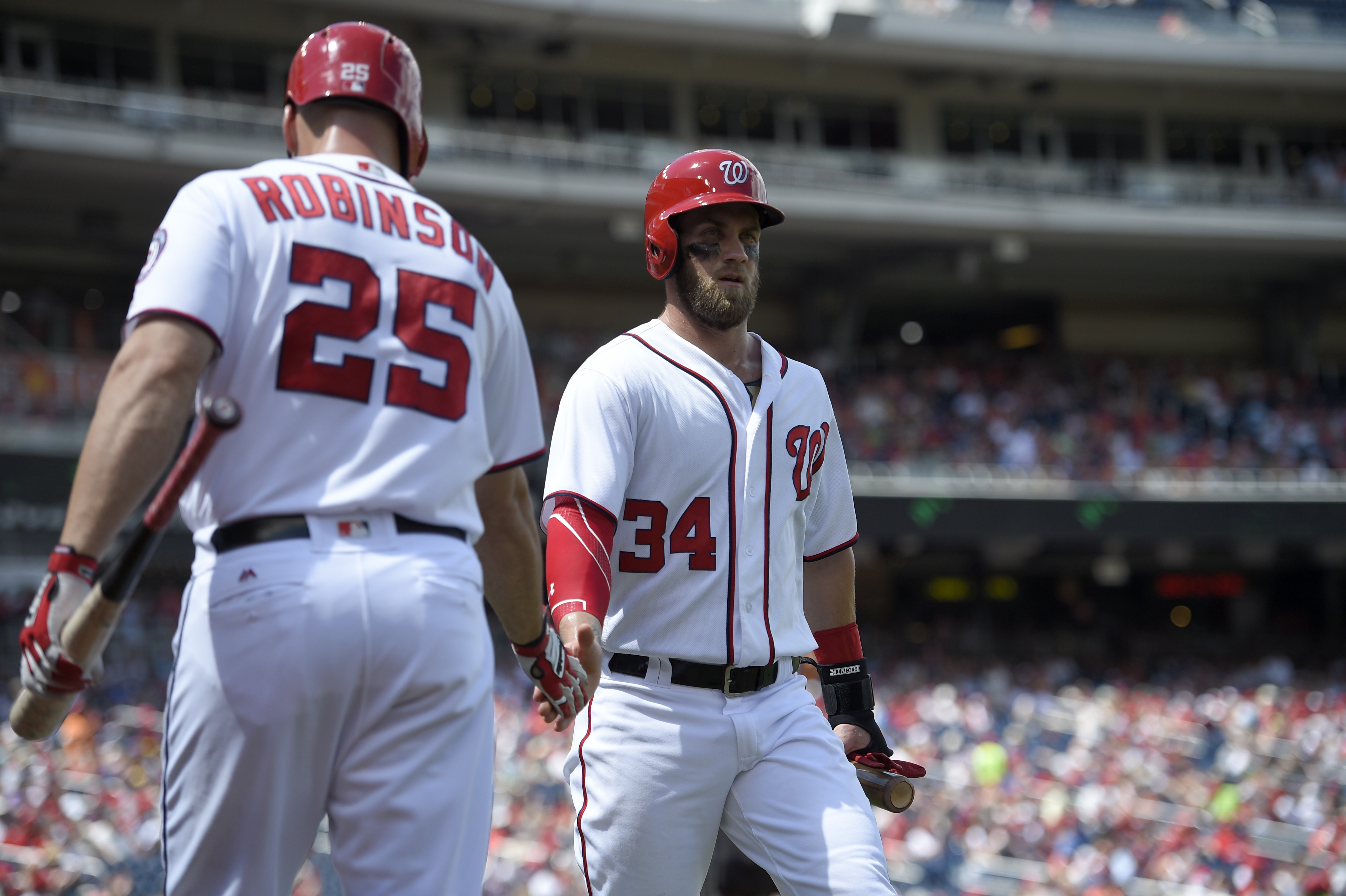 Washington Nationals' Bryce Harper (34) is greeted by Clint Robinson after he scored on a sacrifice fly by Anthony Rendon during the first inning of a baseball game against the Atlanta Braves, Sunday, Aug. 14, 2016, in Washington. (AP Photo/Nick Wass)