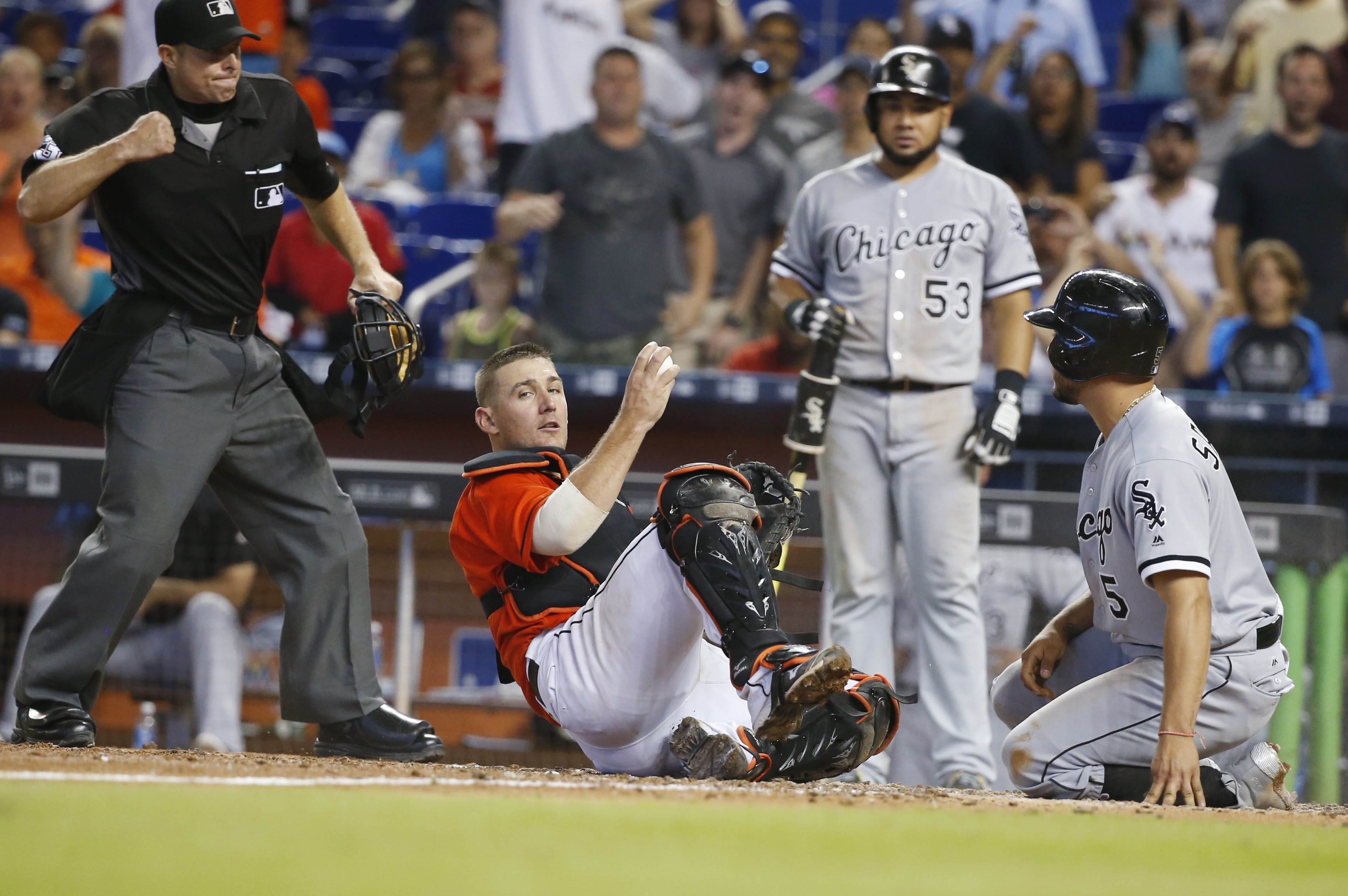 Miami Marlins catcher Jeff Mathis, second from left, holds on to the ball as home plate umpire Tripp Gibson, left, signals the out after Mathis tagged out Chicago White Sox pinch-runner Carlos Sanchez (5) at the plate to end the baseball game, Sunday, Aug