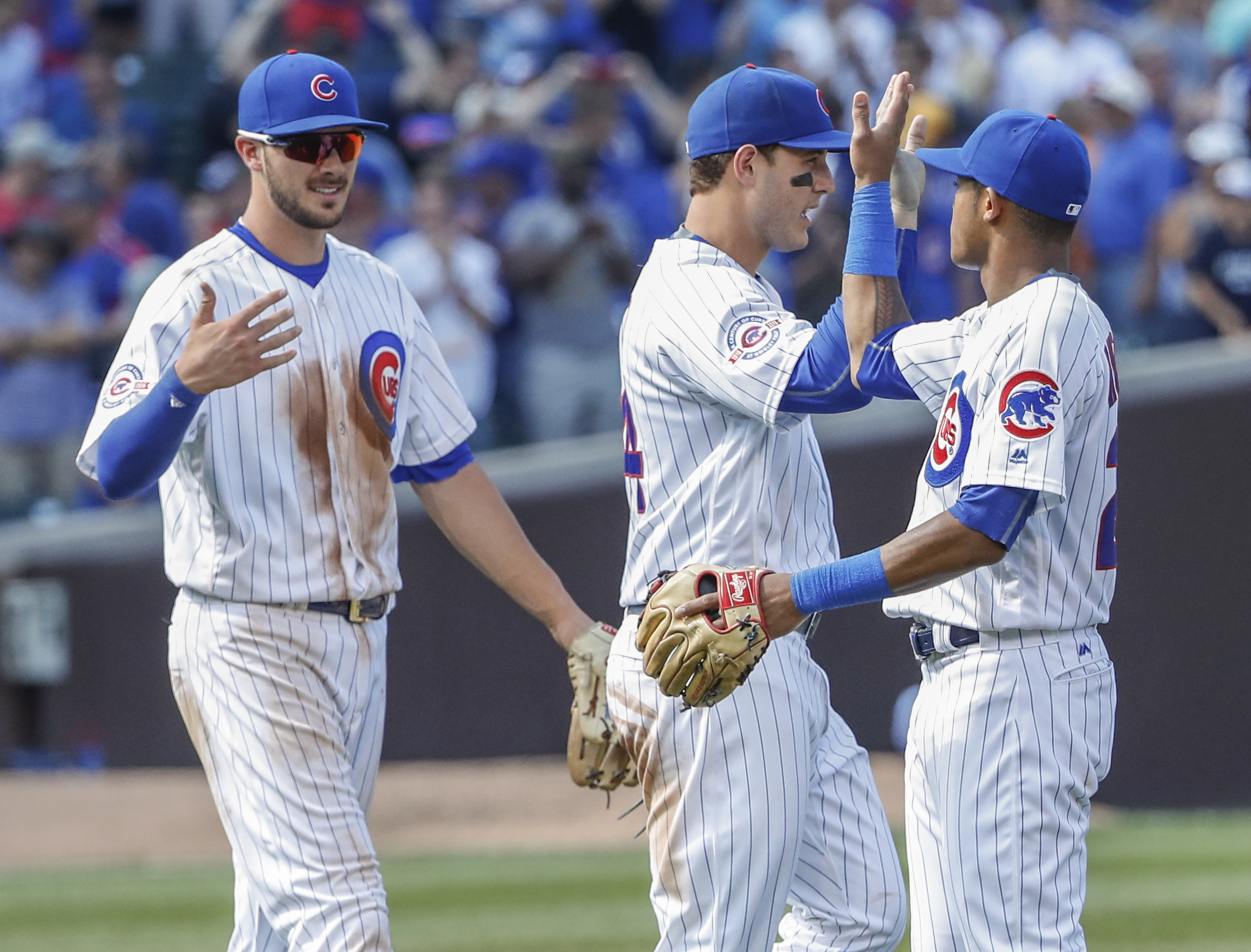 Chicago Cubs' Addison Russell, right, celebrates with Anthony Rizzo, center, and Kris Bryant, left, after the team's 4-0 win against the Milwaukee Brewers in a baseball game, Tuesday, Aug. 16, 2016, at Wrigley Field in Chicago. (AP Photo/Kamil Krzaczynski