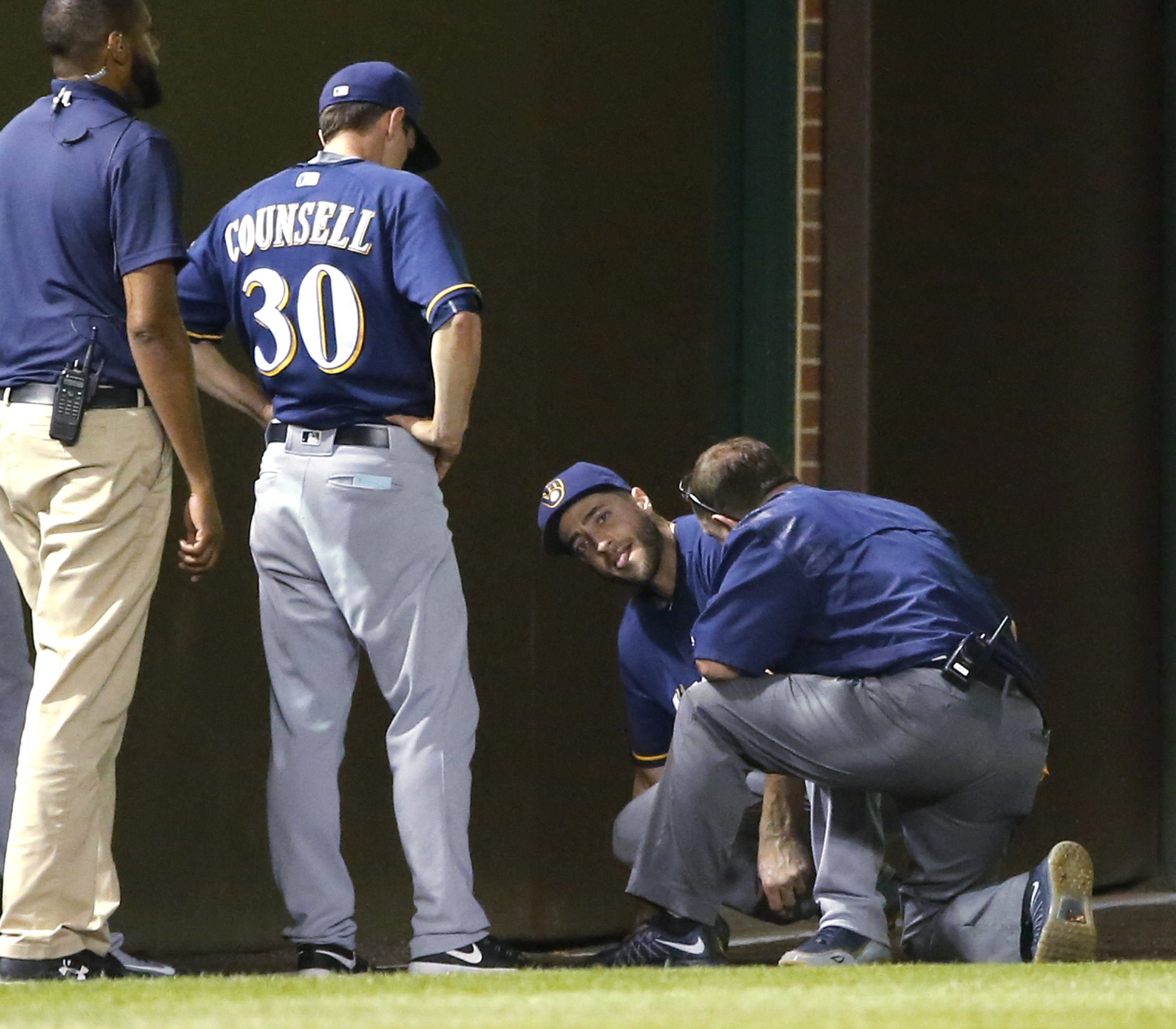 Milwaukee Brewers' Ryan Braun, center, is checked a member off the Brewers' medical staff and manager Craig Counsell after Braun injured his left leg chasing a foul ball by Chicago Cubs' Ben Zobrist during the fourth inning of the second game of a basebal
