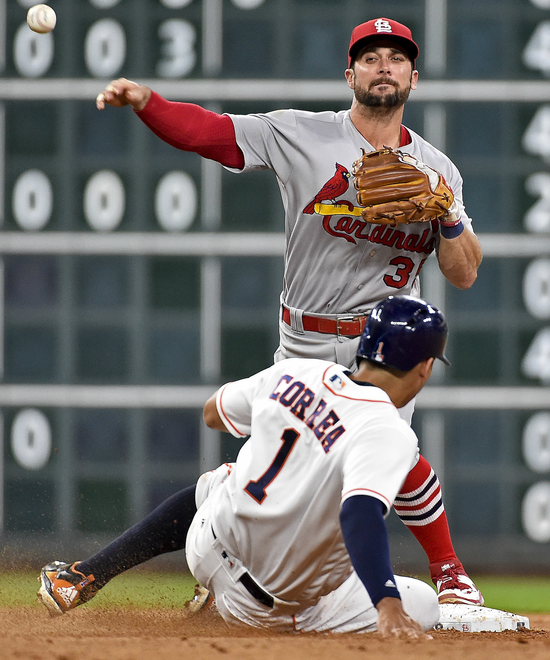 St. Louis Cardinals shortstop Greg Garcia, top, attempts a double play over Houston Astros' Carlos Correa during the seventh inning of a baseball game, Tuesday, Aug. 16, 2016, in Houston. Martin Gonzalez was safe at first. (AP Photo/Eric Christian Smith)