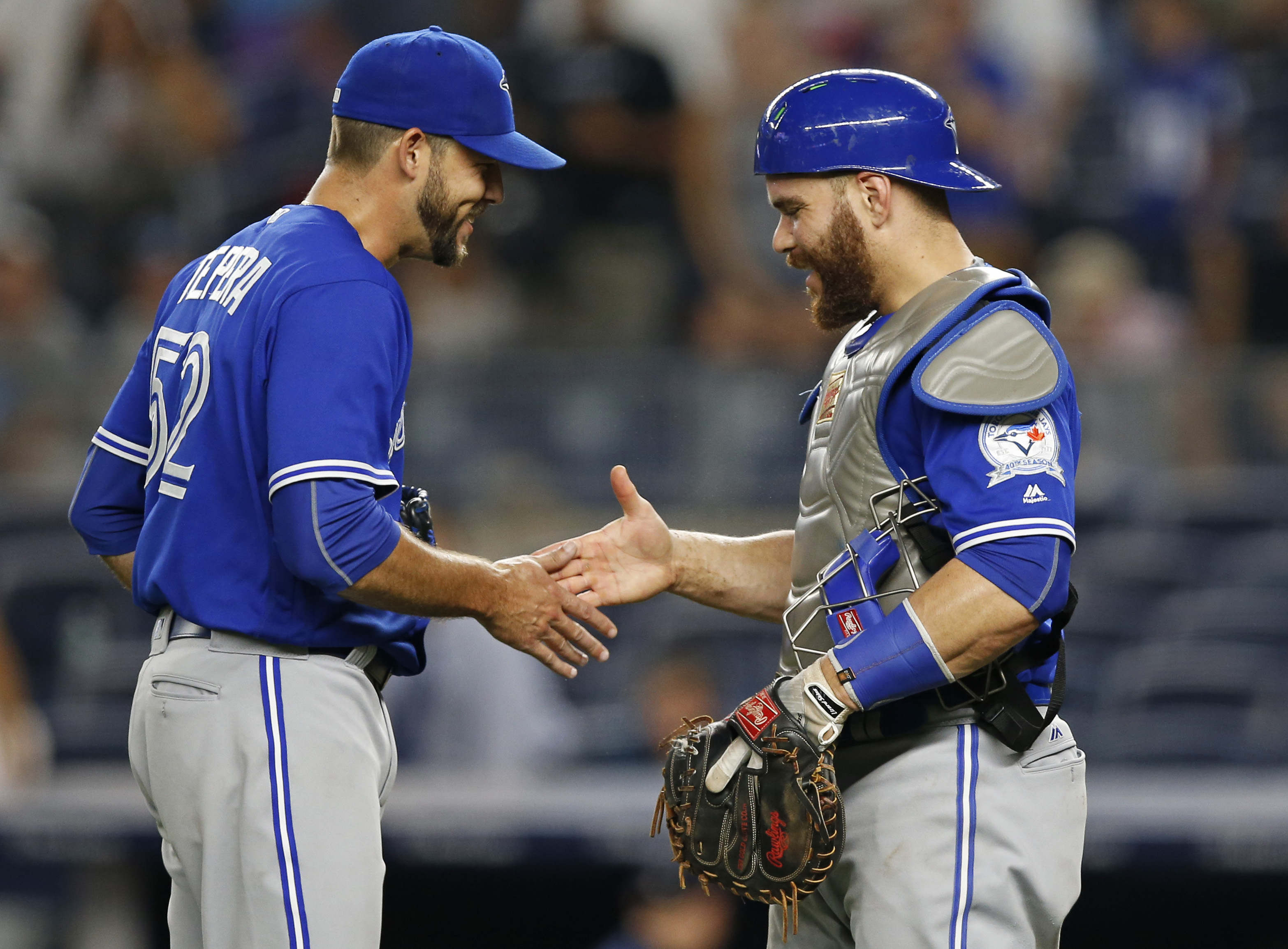 Toronto Blue Jays relief pitcher Ryan Tepera, left, and catcher Russell Martin congratulate one another after Toronto came from behind to defeat the New York Yankees 12-6 in a baseball game in New York, Tuesday, Aug. 16, 2016. Martin hit a two-run home ru
