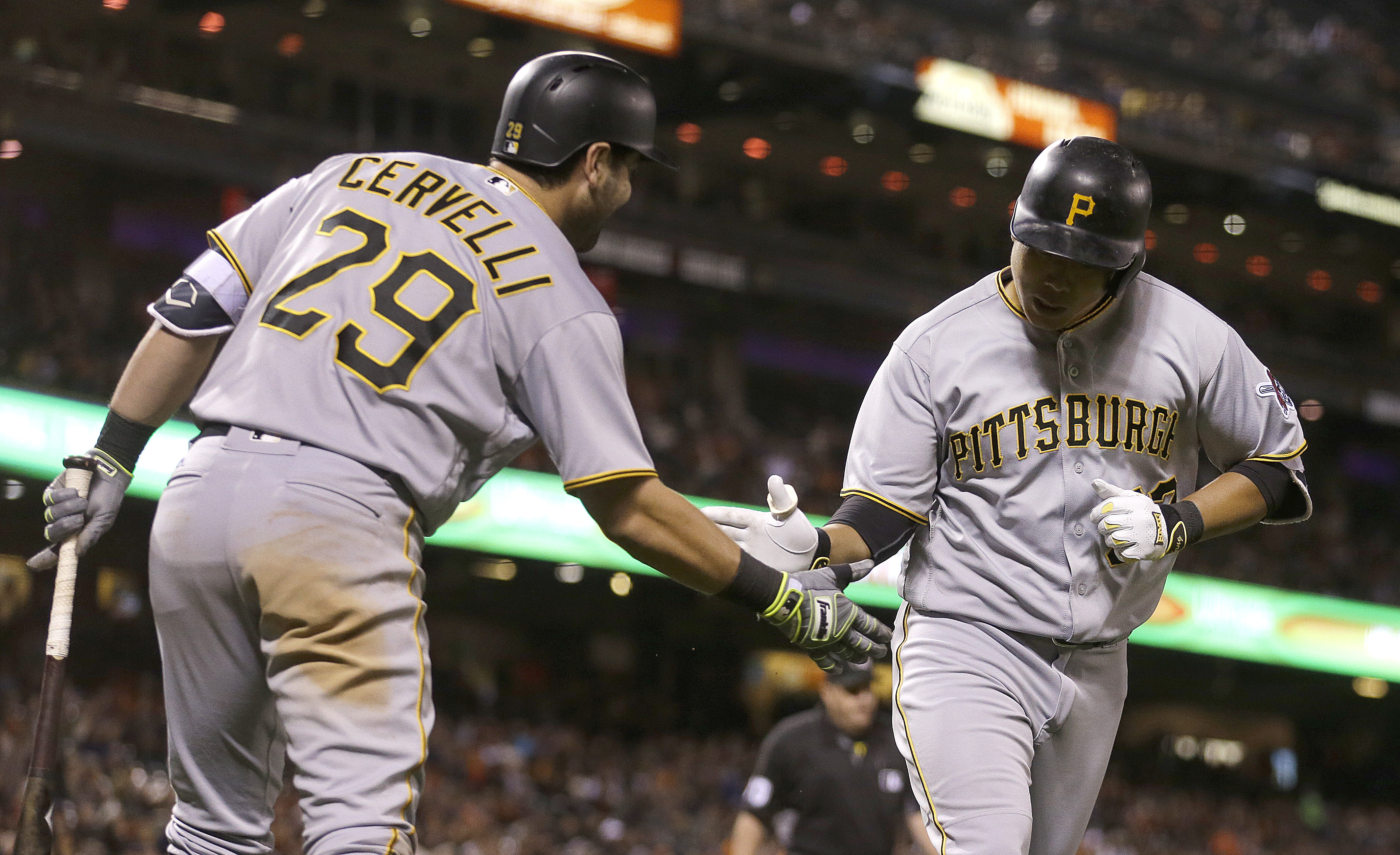Pittsburgh Pirates' Jung Ho Kang, right, is congratulated by Francisco Cervelli (29) after hitting a home run off San Francisco Giants' Derek Law during the eighth inning of a baseball game Tuesday, Aug. 16, 2016, in San Francisco. (AP Photo/Ben Margot)