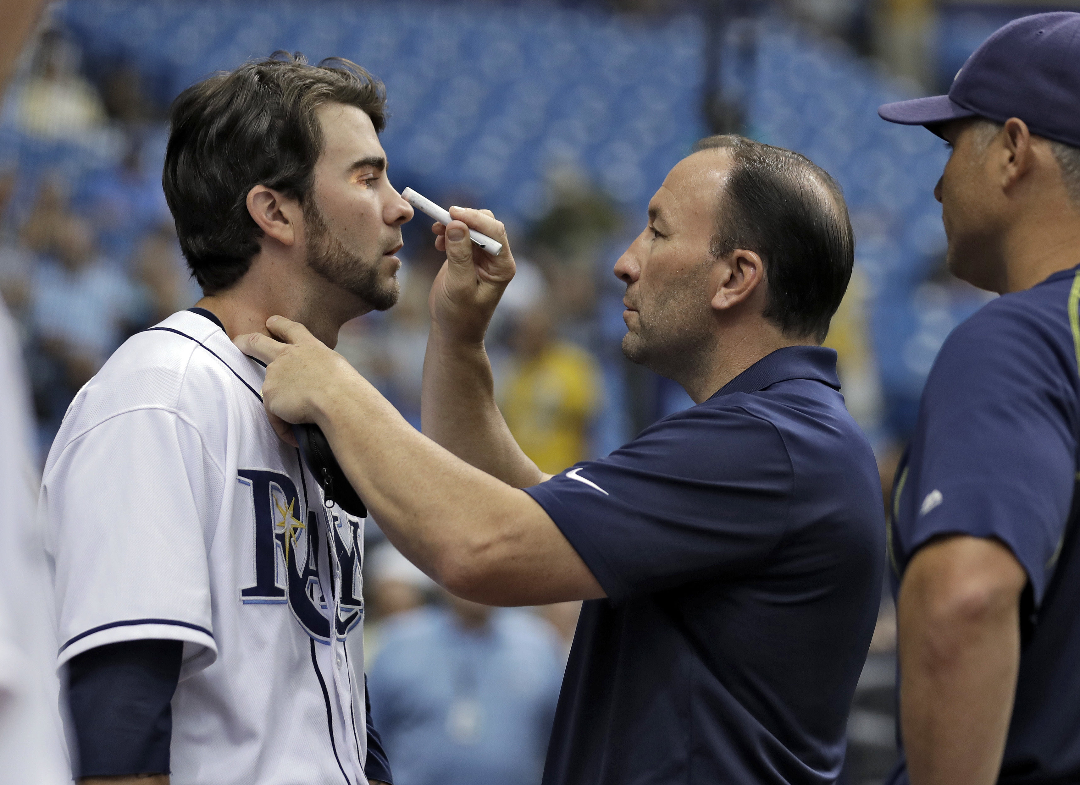 Tampa Bay Rays trainer Ron Porterfield, center, checks on Nick Franklin, left, after Franklin was hit with a bat while in the on-deck circle during the first inning of an interleague baseball game Wednesday, Aug. 17, 2016, in St. Petersburg, Fla. Looking