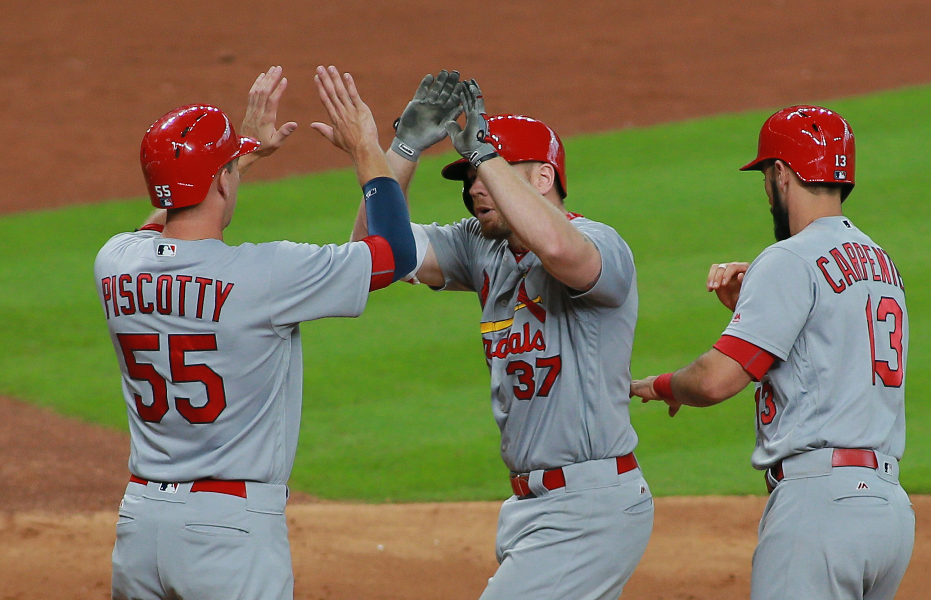 St. Louis Cardinals Brandon Moss (37) is greeted by Stephen Piscotty (55) and Matt Carpenter after hitting a three-run home run against the Houston Astros in the seventh inning of a baseball game Wednesday, Aug. 17, 2016 in Houston. (AP Photo/Richard Cars