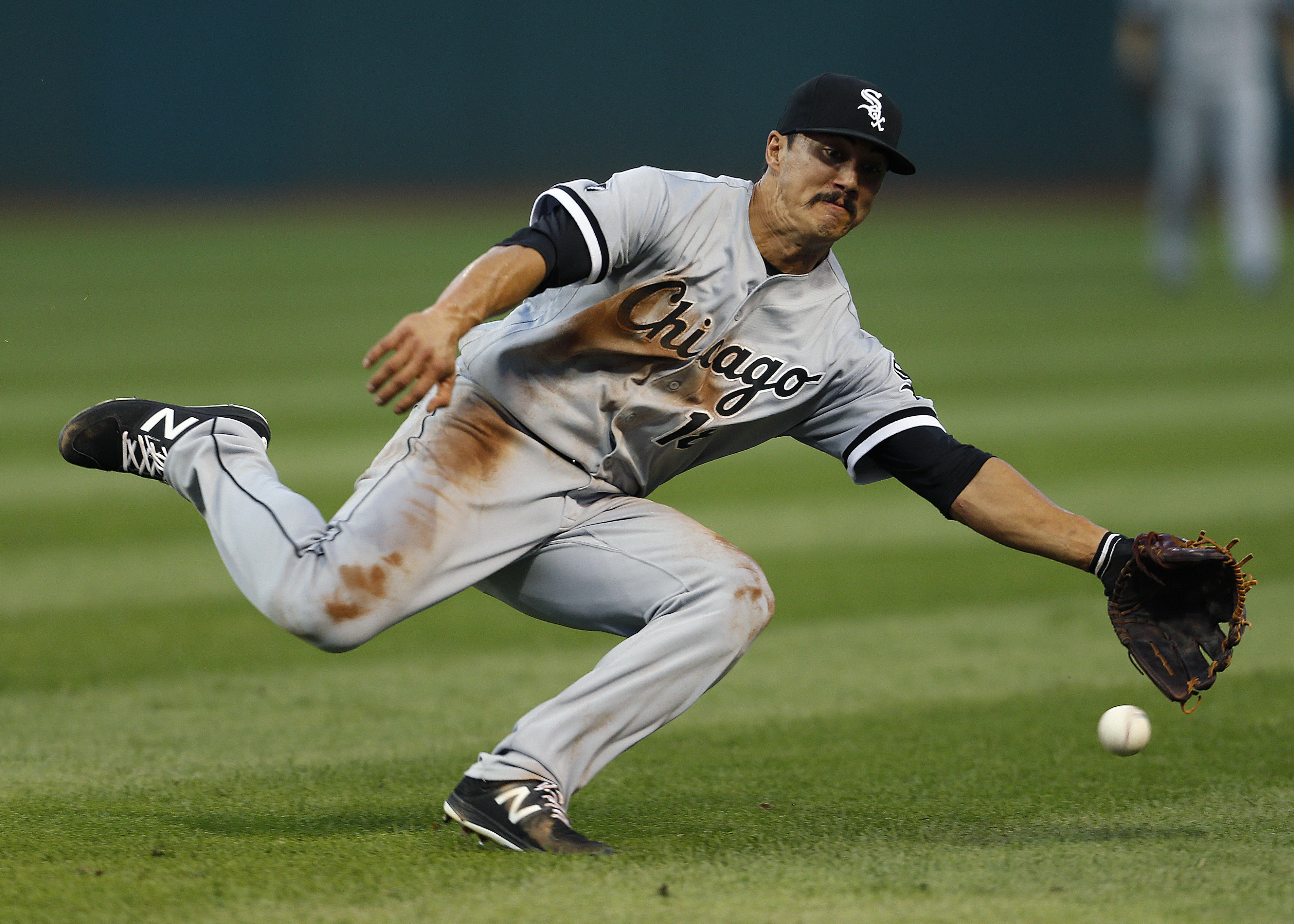 Chicago White Sox's Tyler Saladino tries to field a single by Cleveland Indians' Lonnie Chisenhall during the third inning of a baseball game Wednesday, Aug. 17, 2016, in Cleveland. (AP Photo/Ron Schwane)
