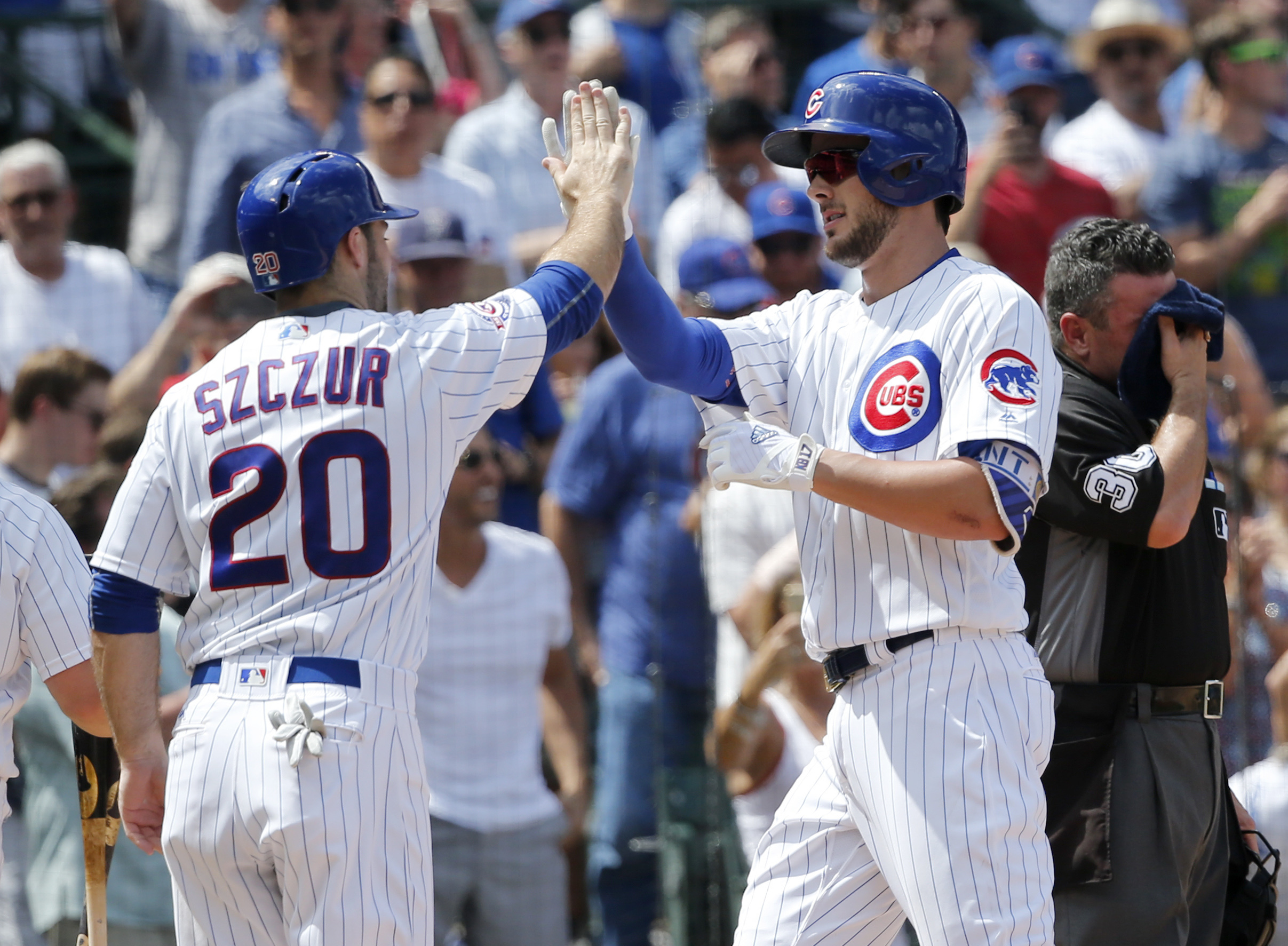 Chicago Cubs' Matt Szczur (20) greets Kris Bryant at home after the pair scored on Bryant's two-run home run off Milwaukee Brewers starting pitcher Zach Davies during the third inning of a baseball game Thursday, Aug. 18, 2016, in Chicago. (AP Photo/Charl
