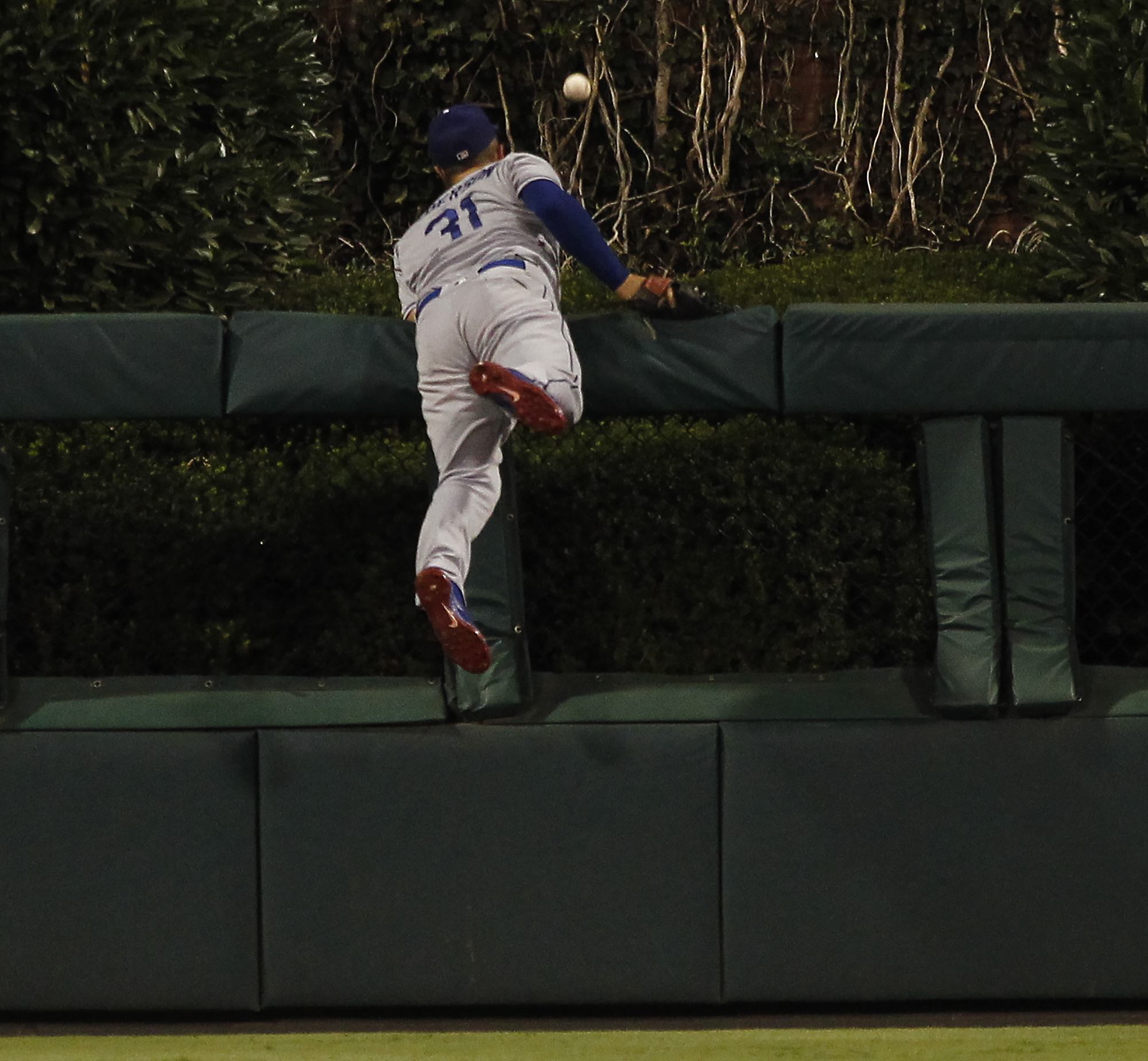 Los Angeles Dodgers' Joc Pederson leans over the fence in center field as a ball hit by Philadelphia Phillies' Maikel Franco for a two-run home run goes past during the seventh inning of a baseball game, Thursday, Aug. 18, 2016, in Philadelphia. (AP Photo