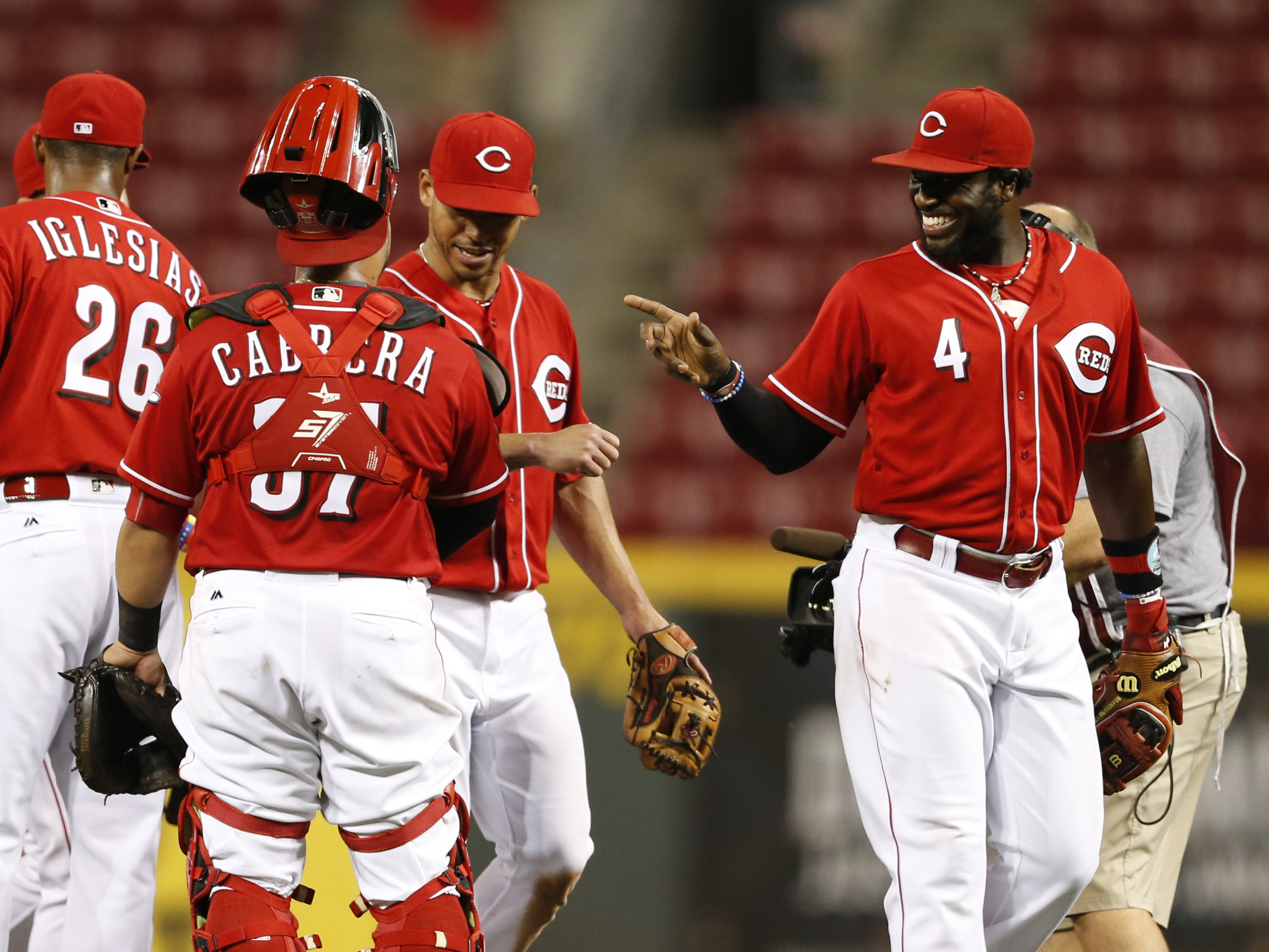 Cincinnati Reds' Brandon Phillips (4) points to catcher Ramon Cabrera, front left, as they celebrate the team's 5-4 win over the Miami Marlins a baseball game, Thursday, Aug. 18, 2016, in Cincinnati. Cabrera hit a three-run home run in the game. (AP Photo
