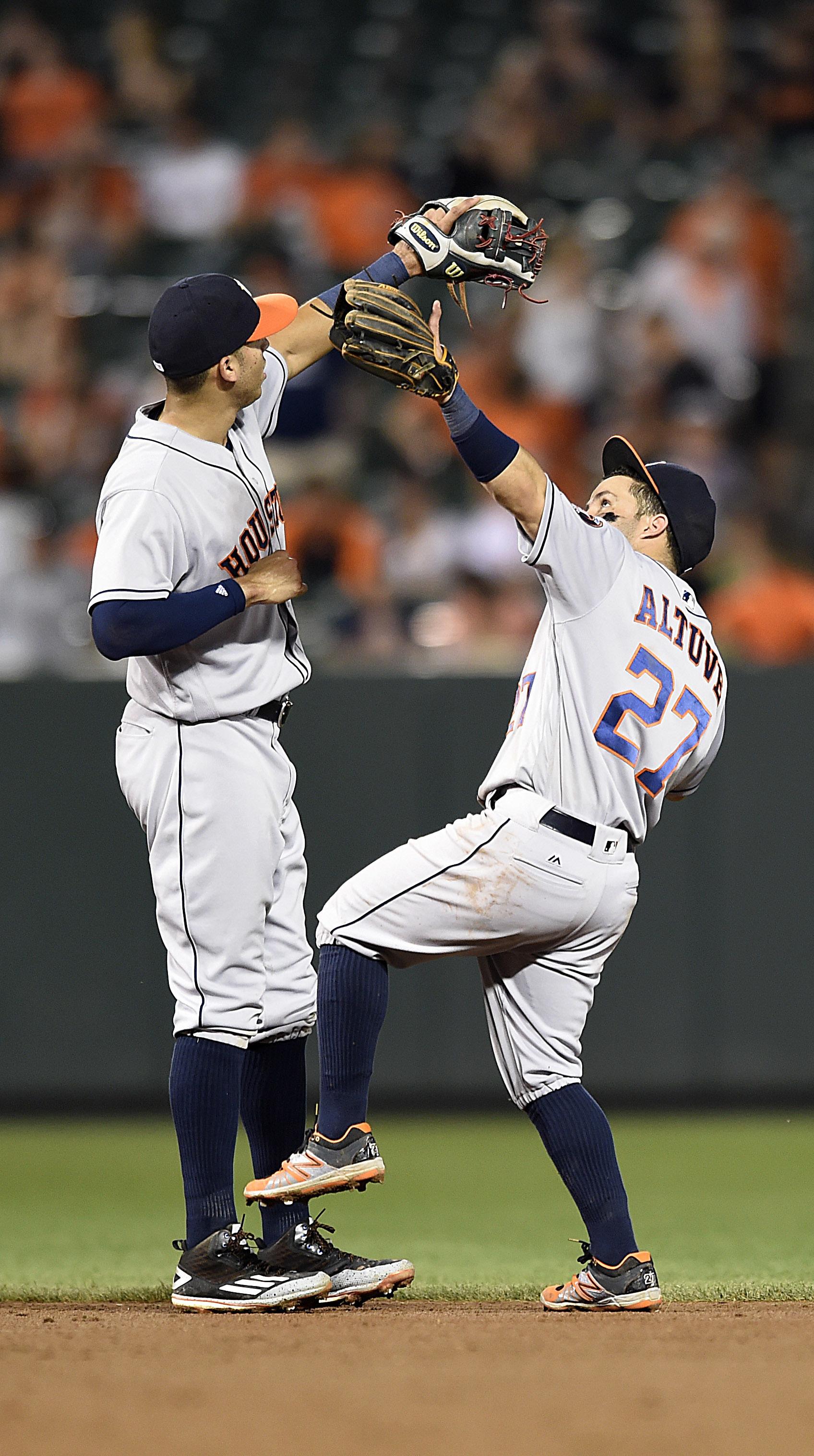 Houston Astros' Carlos Correa, left, and Jose Altuve celebrate the Astros' 15-8 win over the Baltimore Orioles in a baseball game, Friday, Aug. 19, 2016, in Baltimore. (AP Photo/Gail Burton)
