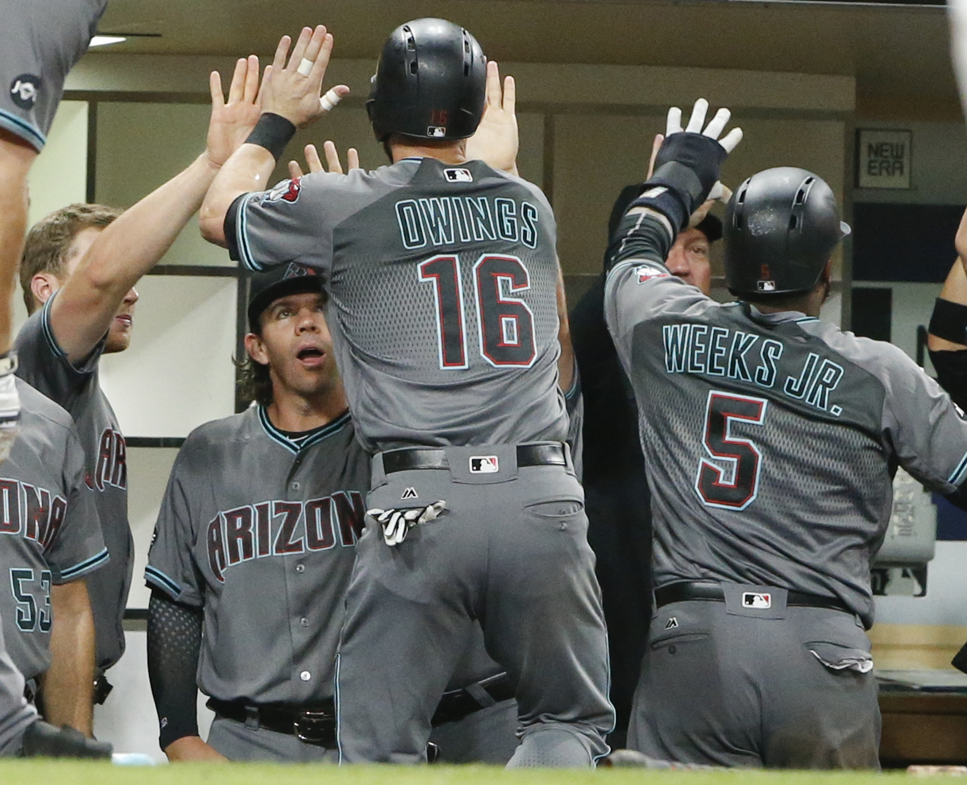 Arizona Diamondbacks' Chris Owings and Rickie Weeks are congratulated after scoring against the San Diego Padres in the eighth inning of a baseball game Friday, Aug. 19, 2016, in San Diego. (AP Photo/Lenny Ignelzi)
