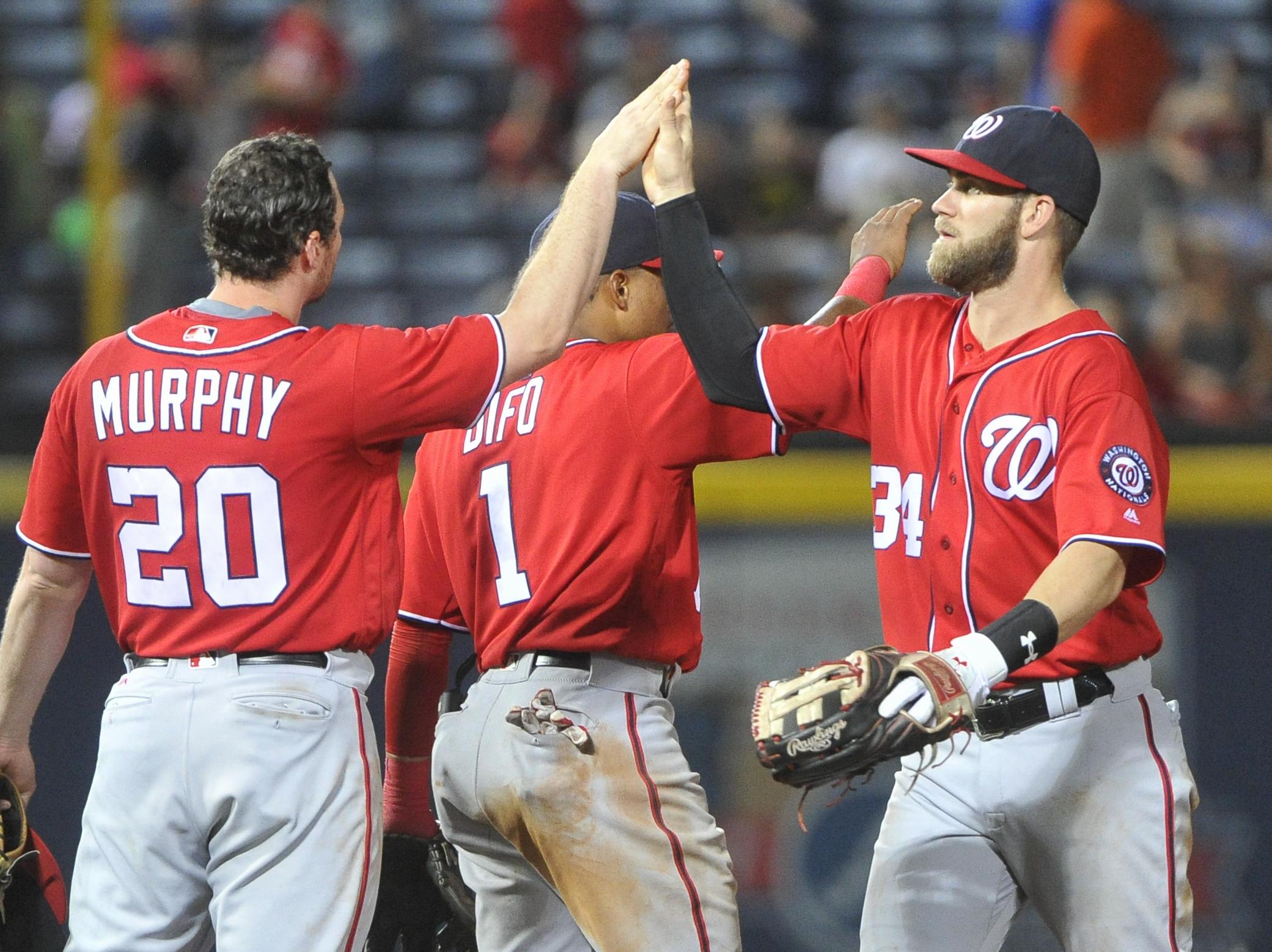 Washington Nationals' Daniel Murphy (20) and Bryce Harper (34) celebrate after the ninth inning of baseball game against the Atlanta Braves, Saturday, Aug. 20, 2016, in Atlanta. Washington won 11-9. (AP Photo/John Amis)
