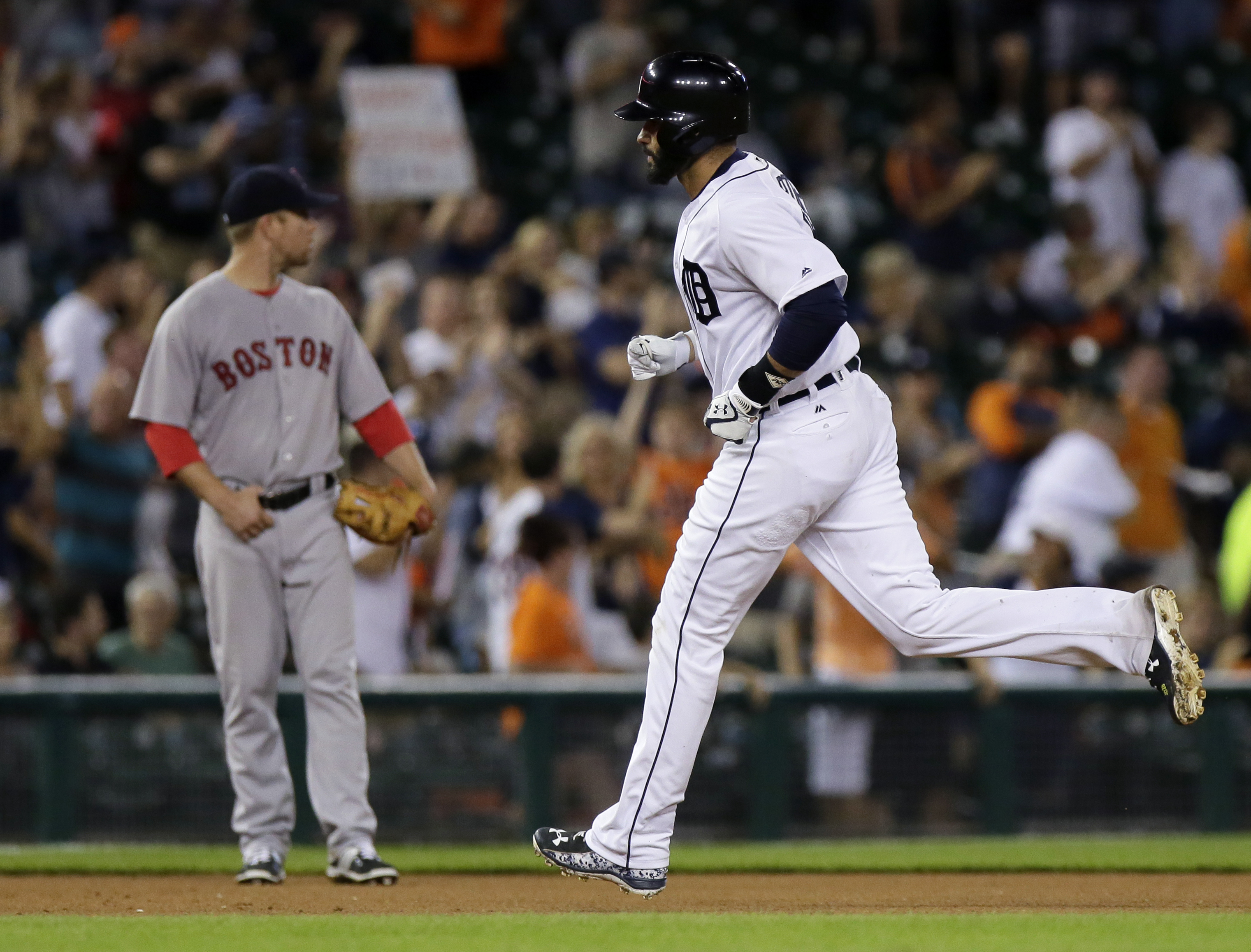Detroit Tigers' J.D. Martinez rounds the bases past Boston Red Sox third baseman Aaron Hill after hitting a solo home run during the seventh inning of a baseball game Saturday, Aug. 20, 2016, in Detroit. (AP Photo/Duane Burleson)