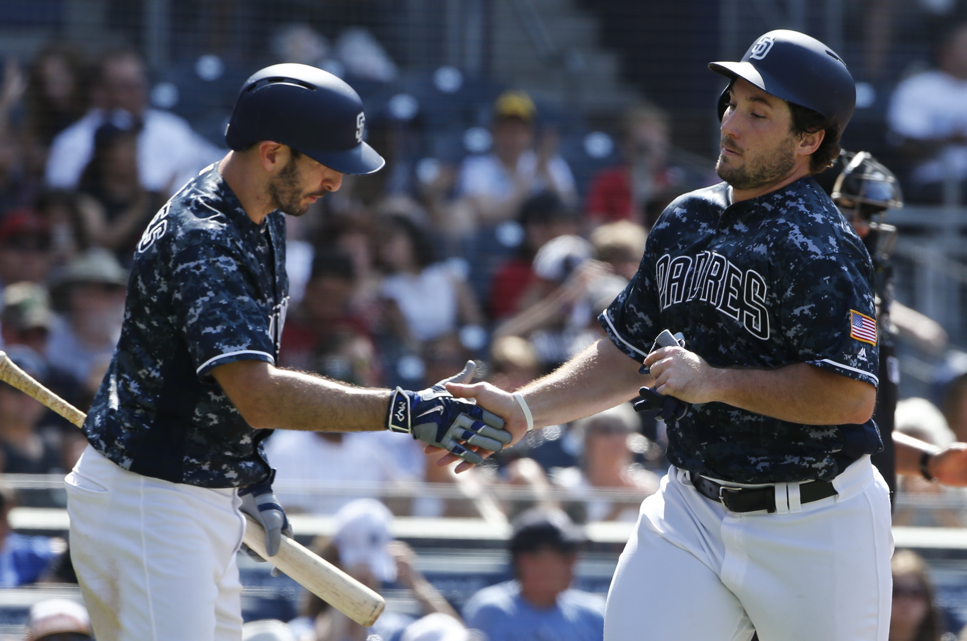 San Diego Padres' Brett Wallace, right, is congratulated by Adam Rosales while scoring against the Arizona Diamondbacks in the sixth inning of a baseball game Sunday, Aug. 21, 2016, in San Diego. (AP Photo/Lenny Ignelzi)
