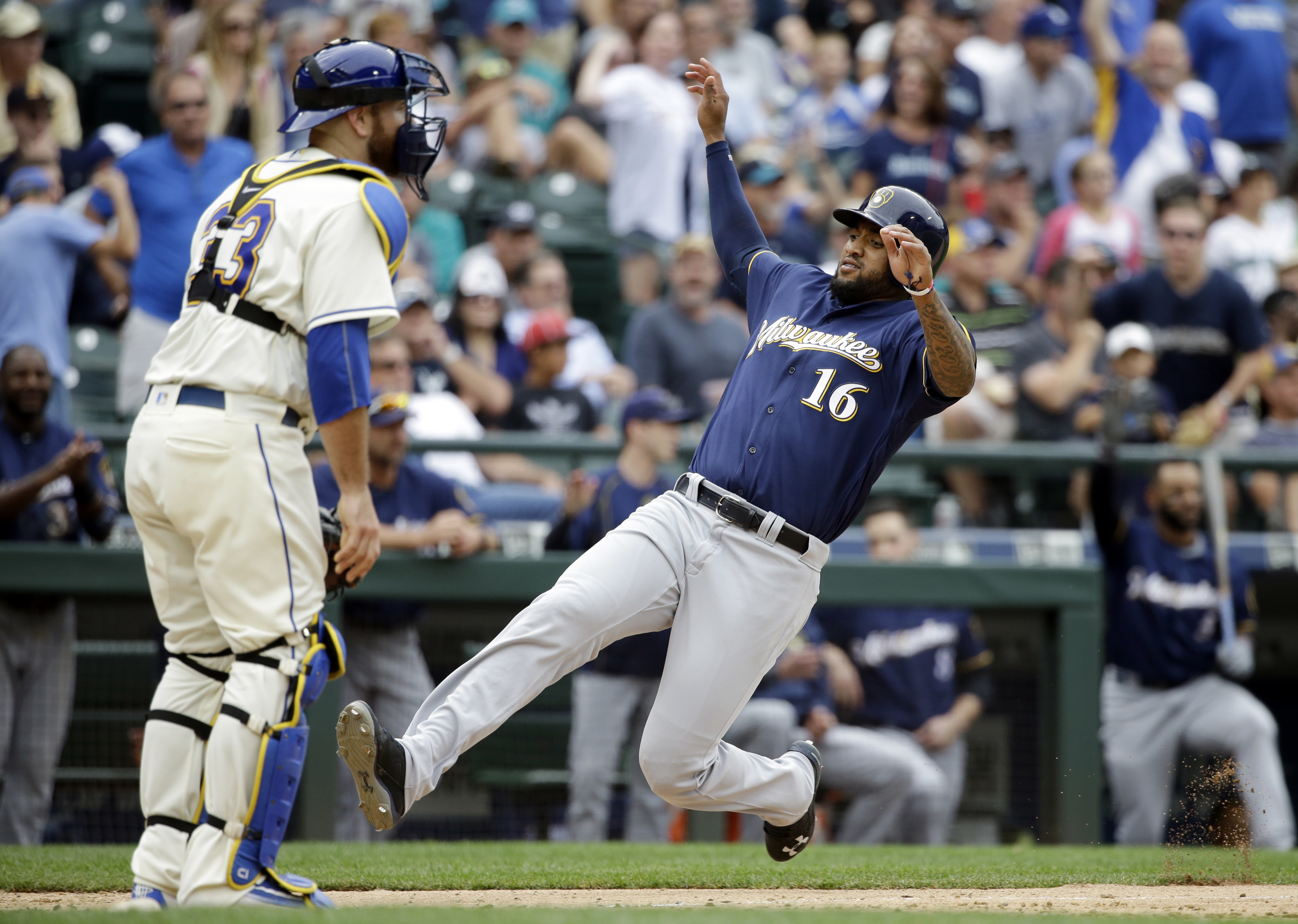 Seattle Mariners catcher Chris Iannetta waits for the throw as Milwaukee Brewers' Domingo Santana slides safely into home to score in the ninth inning of a baseball game, Sunday, Aug. 21, 2016, in Seattle. (AP Photo/Elaine Thompson)