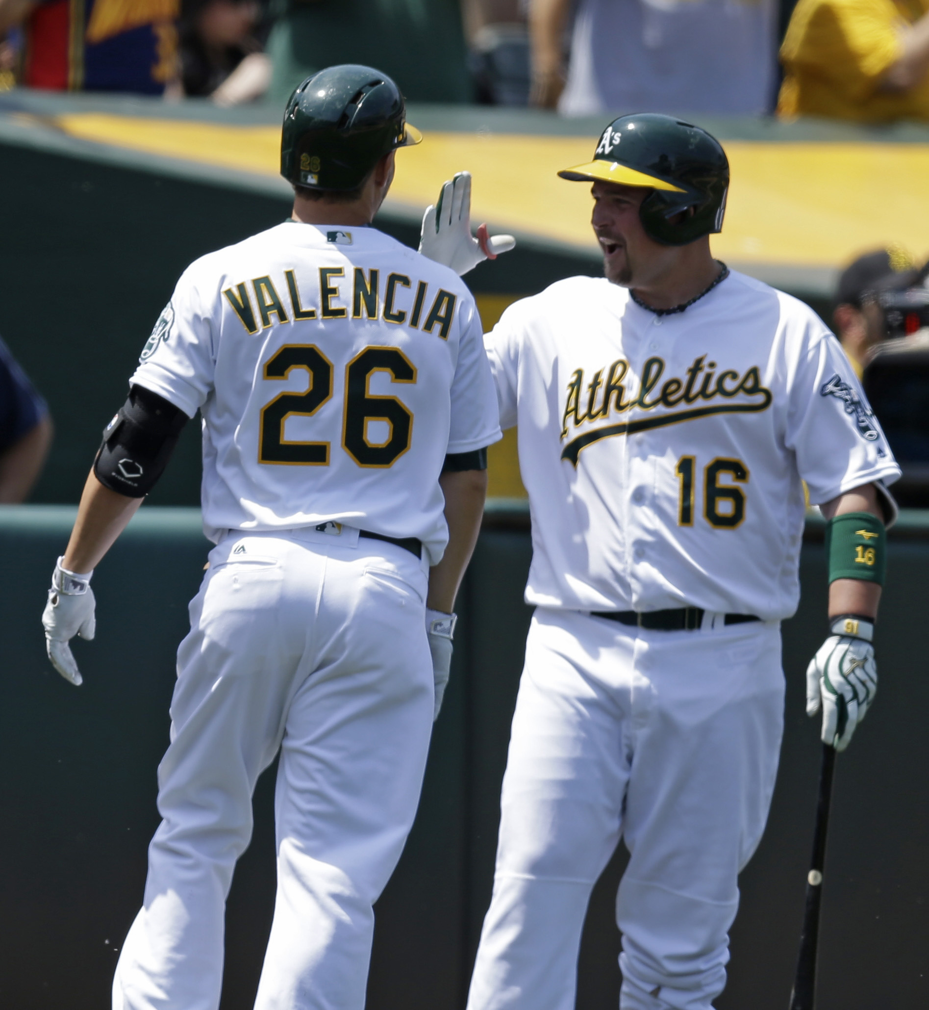 FILE - In this May 28, 2016 file photo Oakland Athletics' Danny Valencia (26) is congratulated by Billy Butler (16) after hitting a home run off Detroit Tigers' Matt Boyd in the fourth inning of a baseball game in Oakland, Calif. Butler and Valencia both