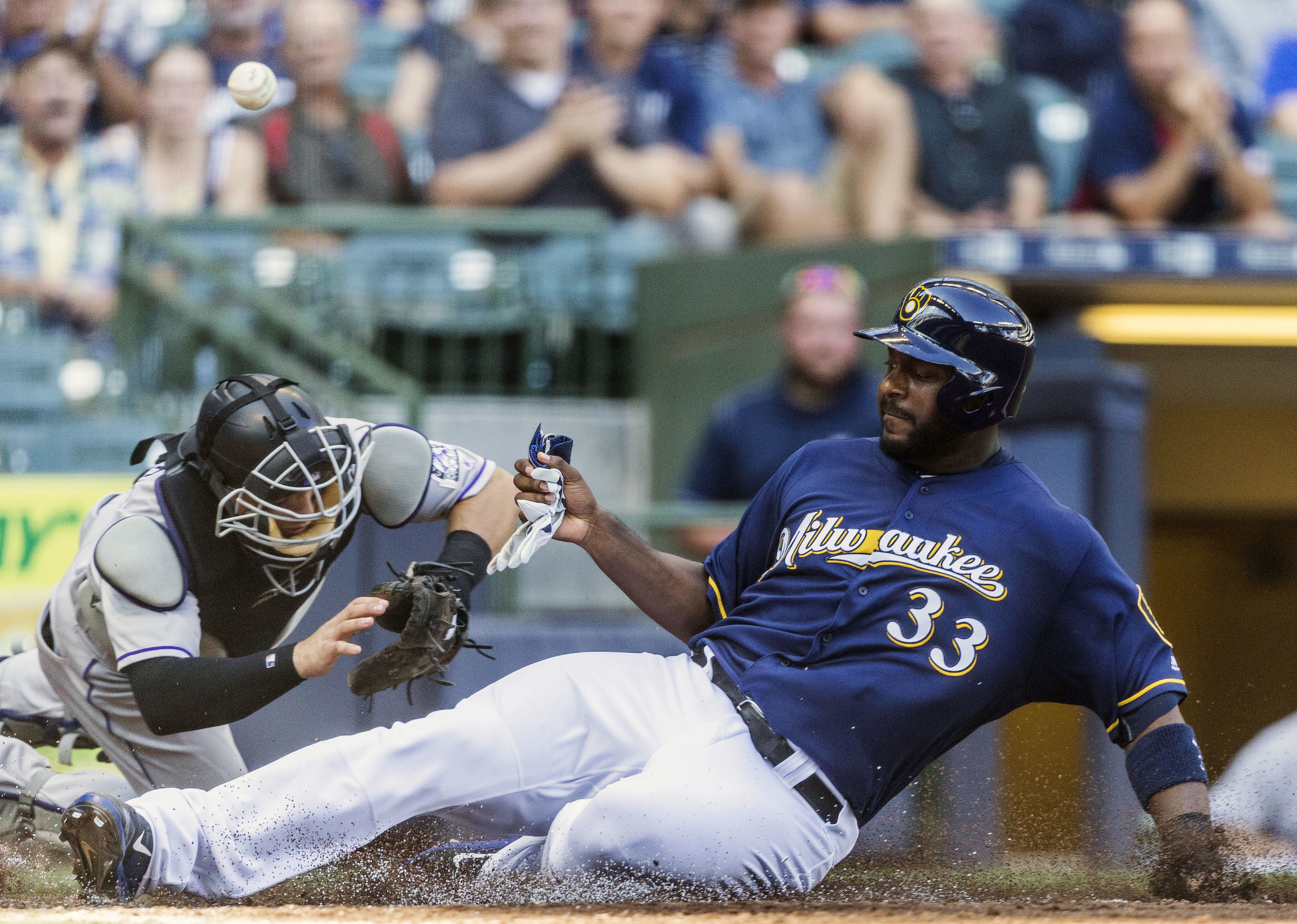 Milwaukee Brewers' Chris Carter is safe at home as Colorado Rockies' Tony Wolters cannot hold on to the ball during a play at the plate in the seventh inning of a baseball game Wednesday, Aug. 24, 2016, in Milwaukee. (AP Photo/Tom Lynn)