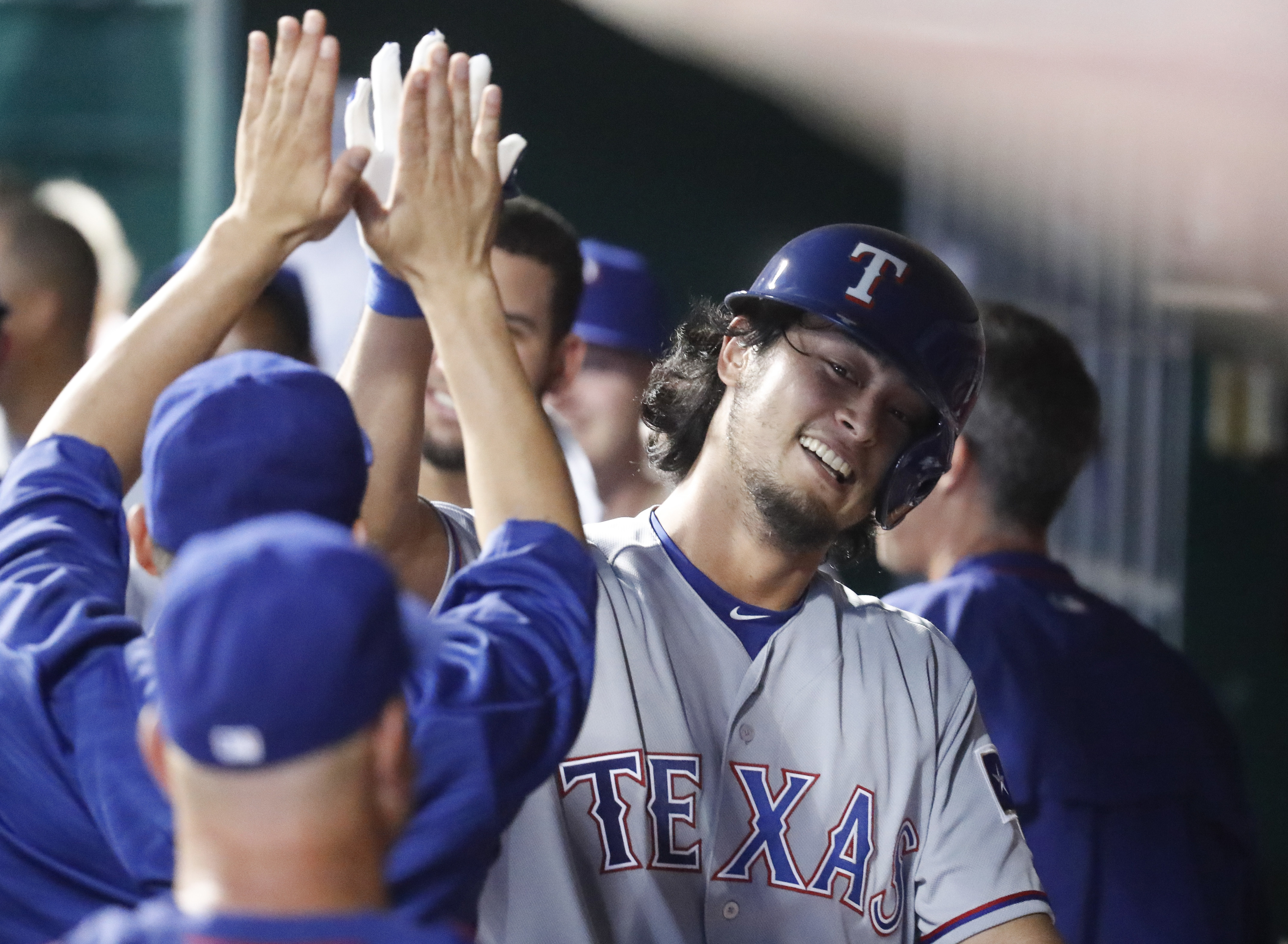 Texas Rangers' Yu Darvish rcelebrates in the dugout after hitting a solo home run off Cincinnati Reds starting pitcher Tim Adleman during the fifth inning of a baseball game, Wednesday, Aug. 24, 2016, in Cincinnati. (AP Photo/John Minchillo)