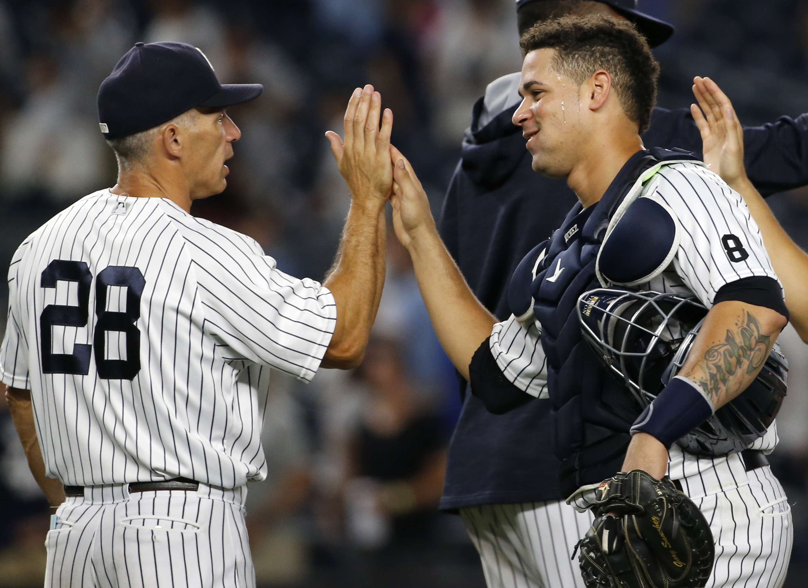 New York Yankees manager Joe Girardi (28) congratulates catcher Gary Sanchez after the Yankees' 14-4 victory over the Baltimore Orioles in a baseball game in New York, Friday, Aug. 26, 2016. Sanchez had three hits, including a two-run home run, and four R