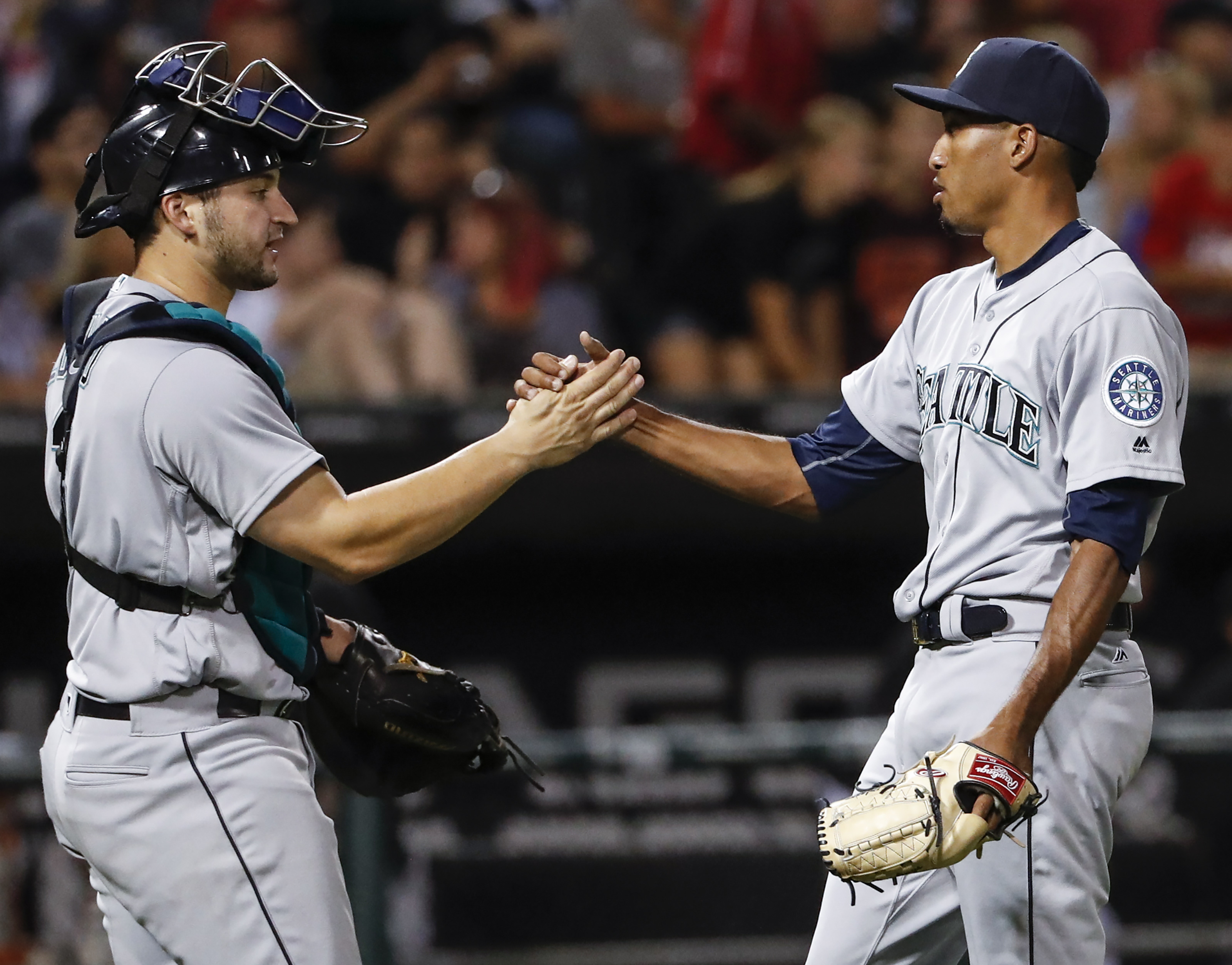 Seattle Mariners' Edwin Diaz, right, and Mike Zunino, left, celebrate a 3-1 win over the Chicago White Sox in a baseball game, Friday, Aug. 26, 2016, in Chicago. (AP Photo/Kamil Krzaczynski)