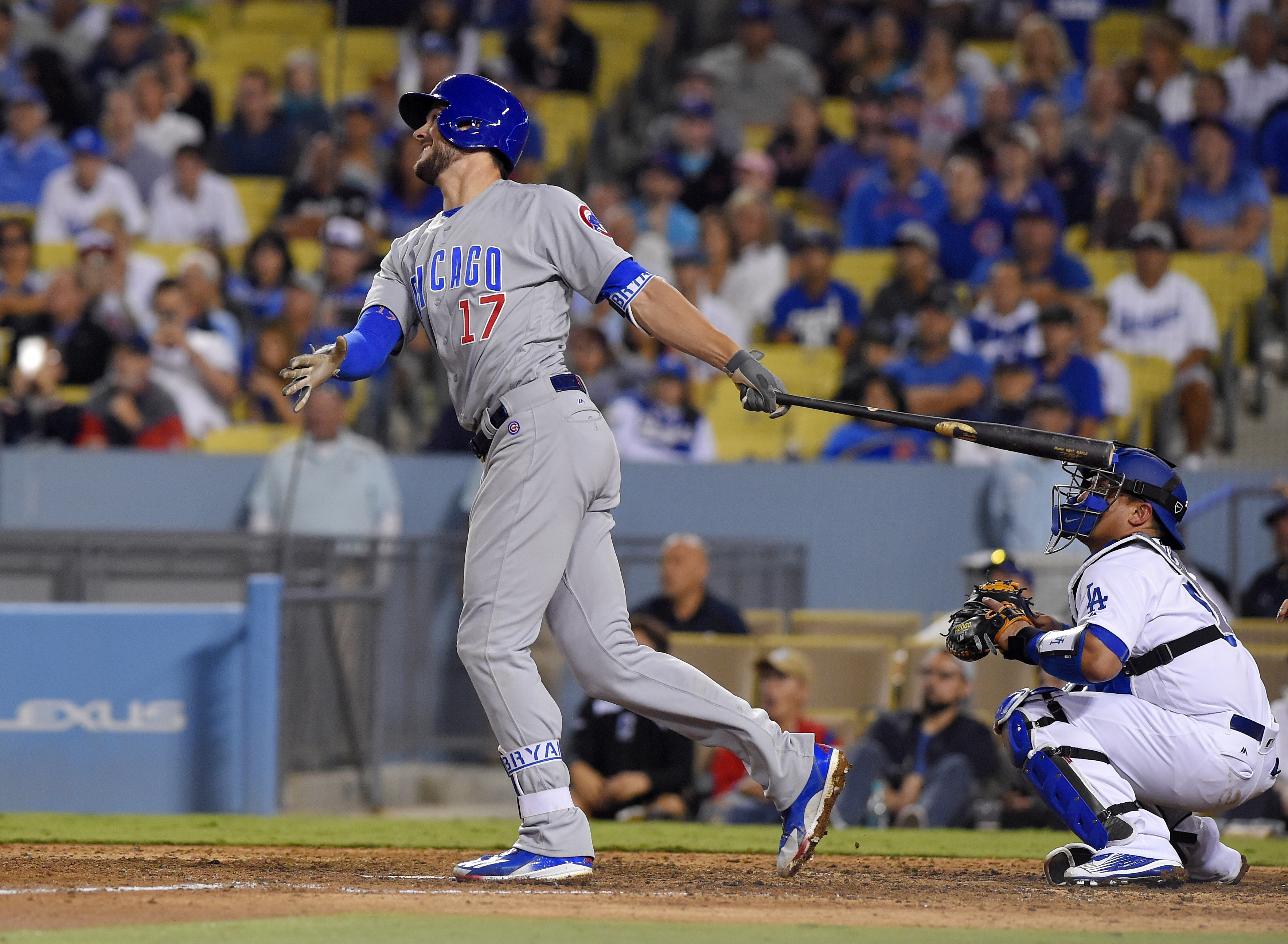 Chicago Cubs' Kris Bryant, left, follows through on a two-run home run as Los Angeles Dodgers catcher Carlos Ruiz watches during the 10th inning of a baseball game, Friday, Aug. 26, 2016, in Los Angeles. (AP Photo/Mark J. Terrill)