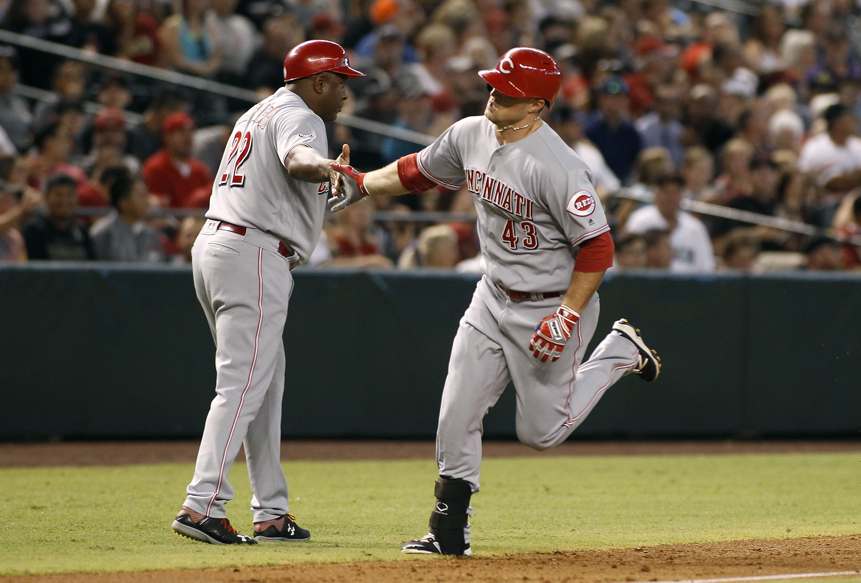 Cincinnati Reds' Scott Schebler (43) is congratulated by third base coach Billy Hatcher as he rounds the base after hitting a three-run home run against the Arizona Diamondbacks during the second inning of a baseball game, Saturday, Aug. 27, 2016, in Phoe