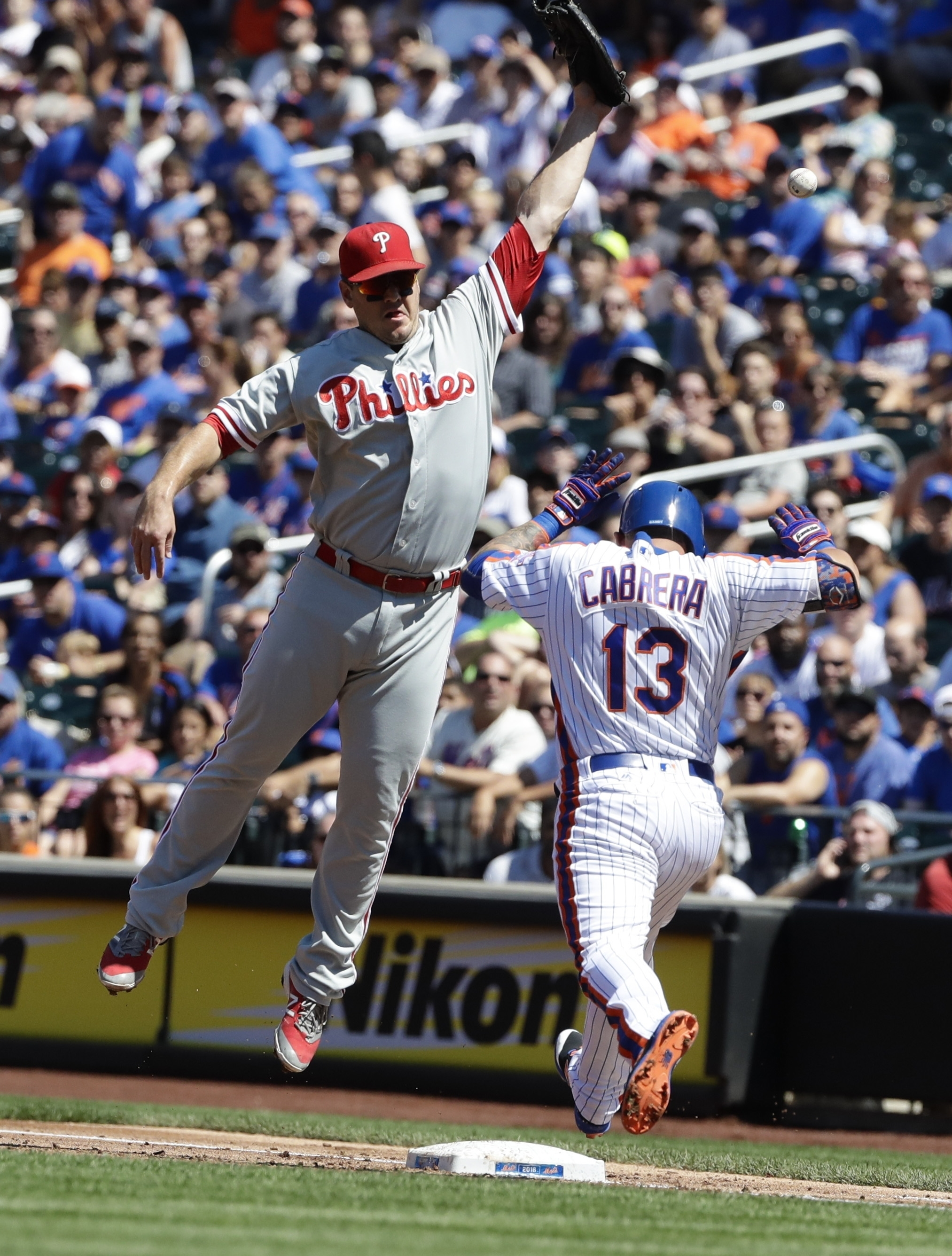 Philadelphia Phillies first baseman Tommy Joseph loses control of the ball as New York Mets' Asdrubal Cabrera (13) beats the throw to first base of a baseball game Sunday, Aug. 28, 2016, in New York. Cabrera was injured on the play. (AP Photo/Frank Frankl