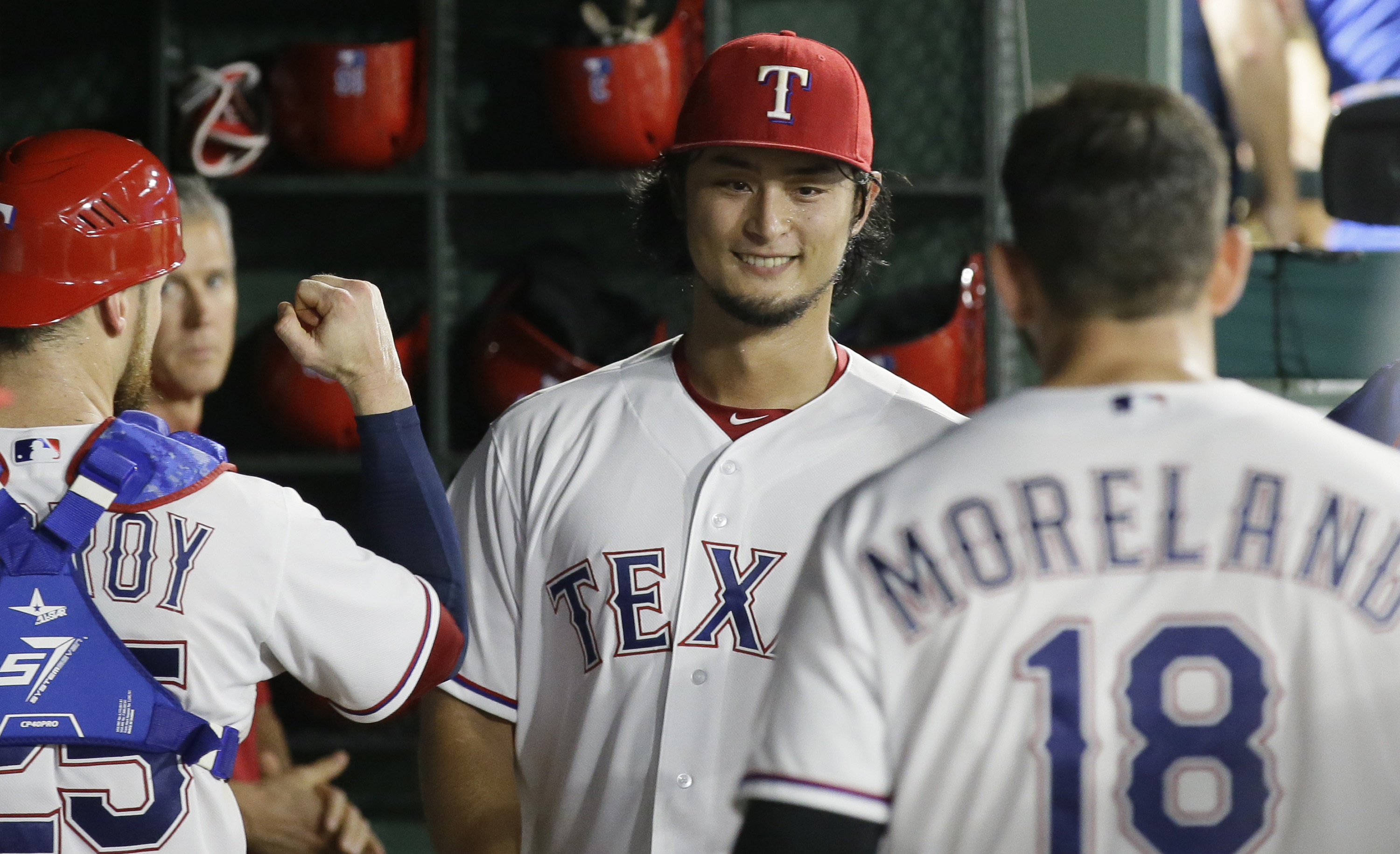 Texas Rangers starting pitcher Yu Darvish of Japan, center, is congratulated by teammates Jonathan Lucroy (25) and Mitch Moreland (18) in the dugout after the sixth inning of a baseball game against the Seattle Mariners in Arlington, Texas, Monday, Aug. 2