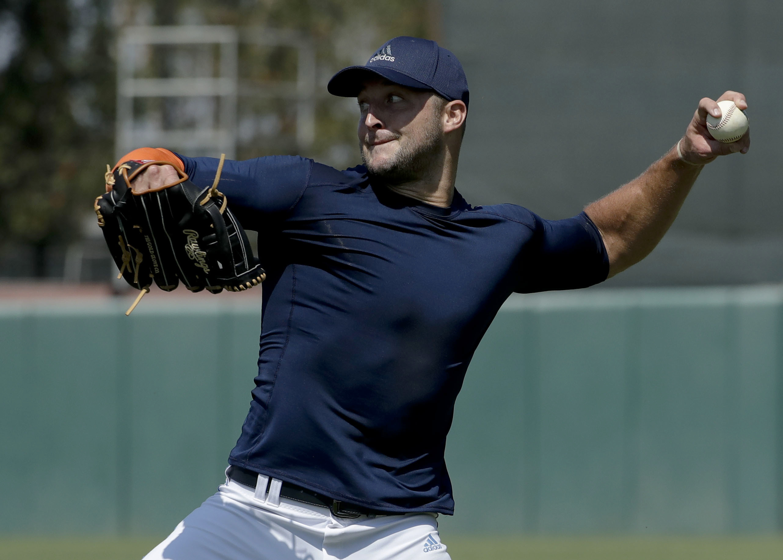 Former NFL quarterback, Tim Tebow throws a ball for baseball scouts and the media during a showcase on the campus of the University of Southern California, Tuesday, Aug. 30, 2016 in Los Angeles. The Heisman Trophy winner works out for a big gathering of s
