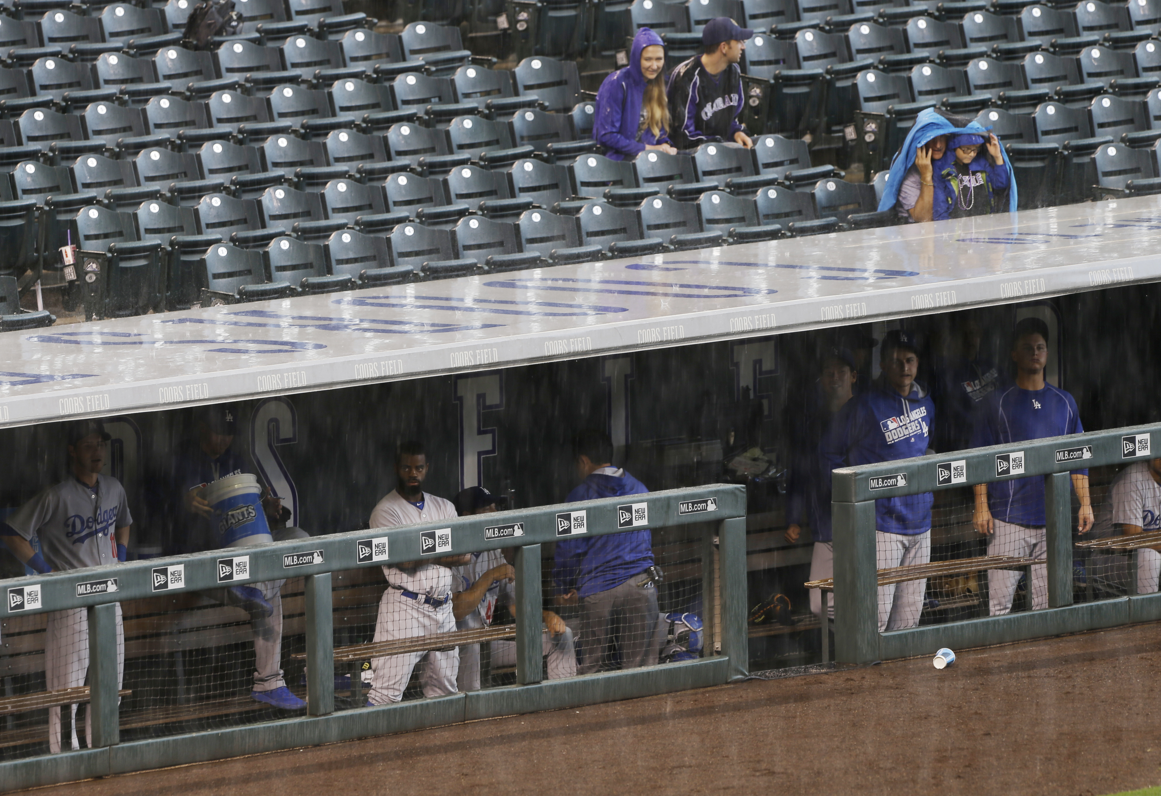 Members of the Los Angeles Dodgers hang out in the dugout during a rain delay before the team's baseball game against the Colorado Rockies on Tuesday, Aug. 30, 2016, in Denver. (AP Photo/Jack Dempsey)