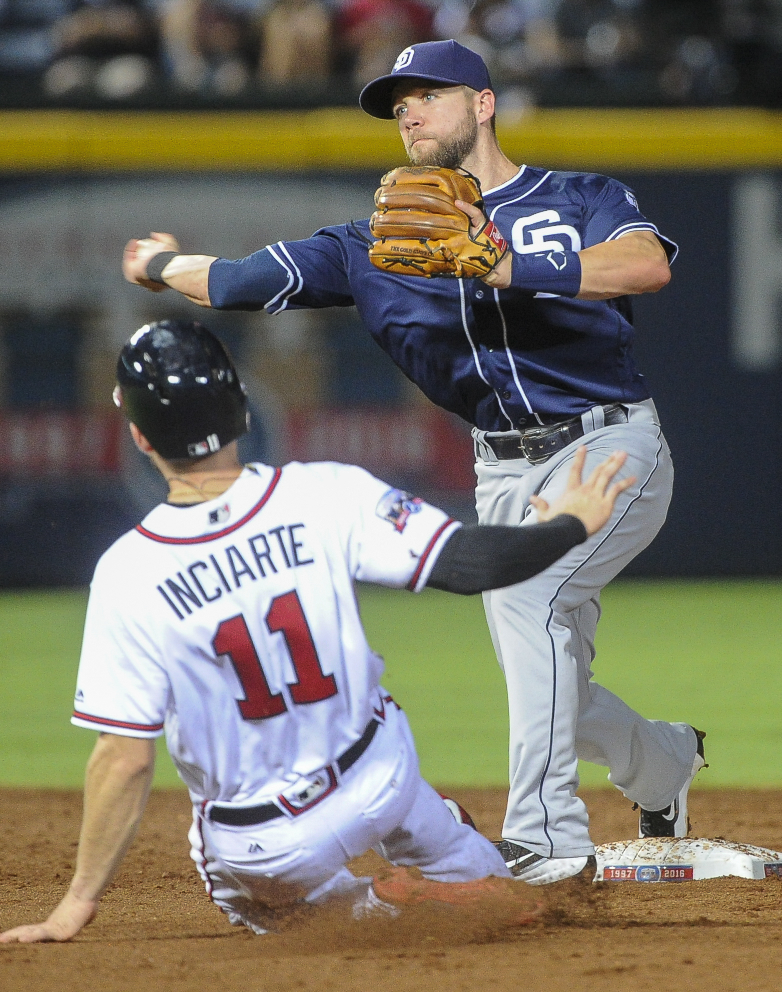 San Diego Padres second baseman Ryan Schimpf turns a double play as he forces out Atlanta Braves' Ender Inciarte (11) on a throw from pitcher Christian Friedrich and throws out Adonis Garcia at first base during the sixth inning of a baseball game, Tuesda