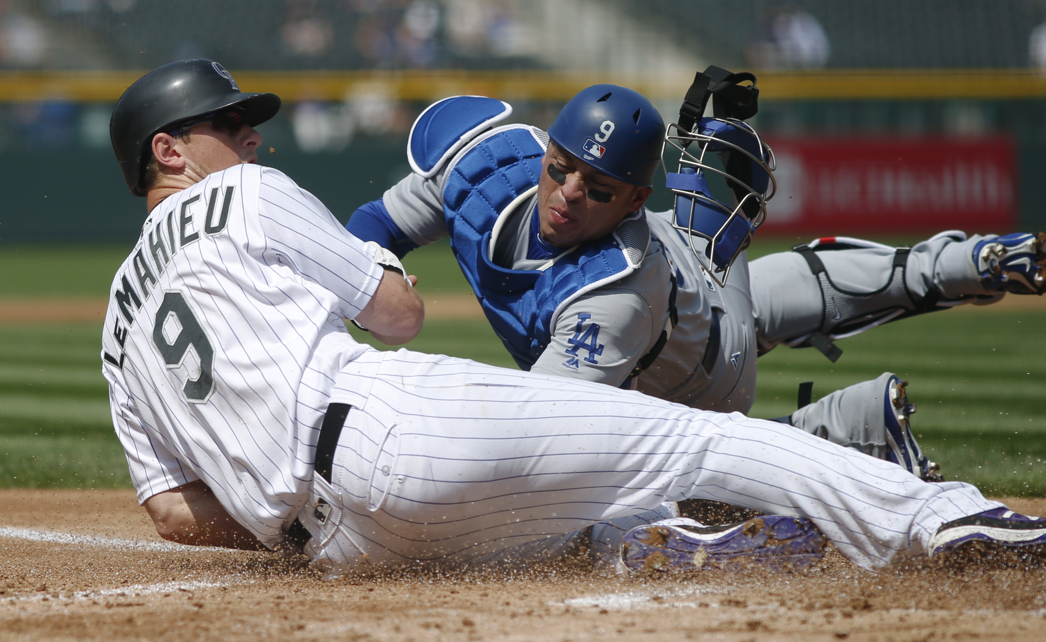 Colorado Rockies' DJ LeMahieu, front, avoids the tag by Los Angeles Dodgers catcher Carlos Ruiz to score on a double hit by Nolan Arenado in the first inning of the first baseball game of a doubleheader Wednesday, Aug. 31, 2016, in Denver. (AP Photo/David