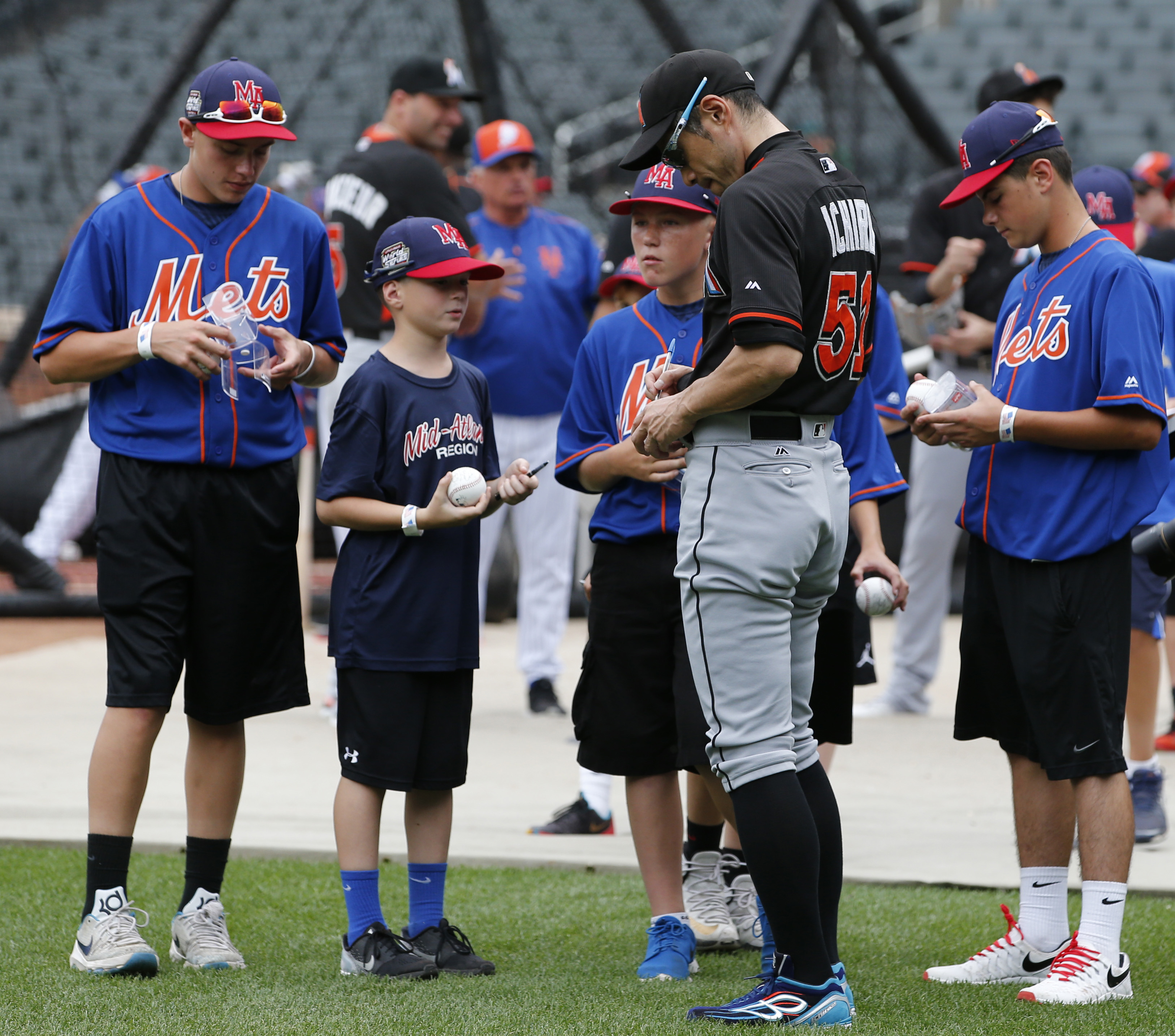 Miami Marlins' Ichiro Suzuki (51) signs autographs for members of the Little League World Series winning team from Endwell, N.Y., during batting practice before a baseball game between the New York Mets and the Marlins, Wednesday, Aug. 31, 2016, in New Yo