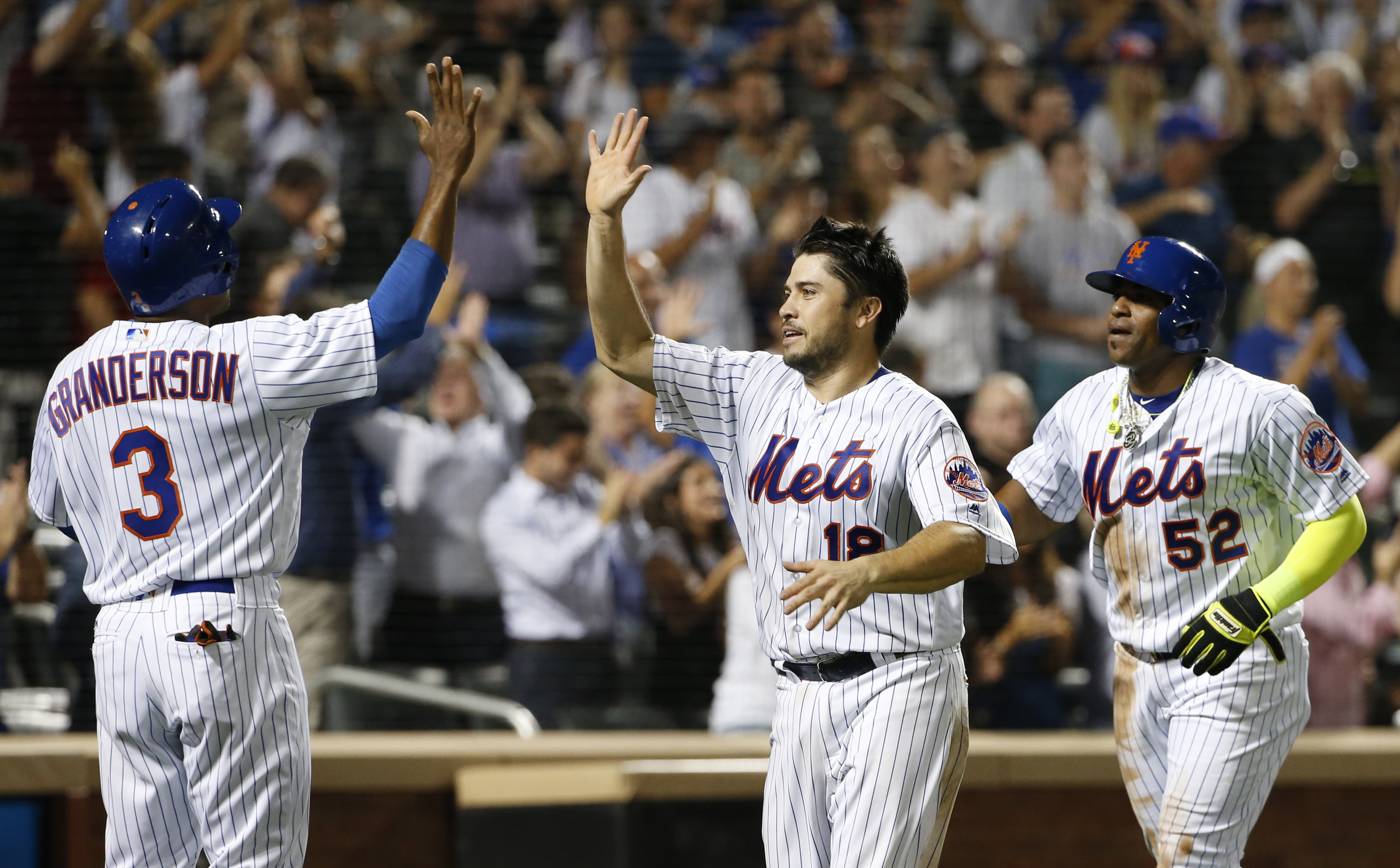 New York Mets' Curtis Granderson (3) greets Travis d'Arnaud (18) and Yoenis Cespedes (52) after all three scored on Kelly Johnson's eighth-inning double in a baseball game against the Miami Marlins, Wednesday, Aug. 31, 2016, in New York. (AP Photo/Kathy W