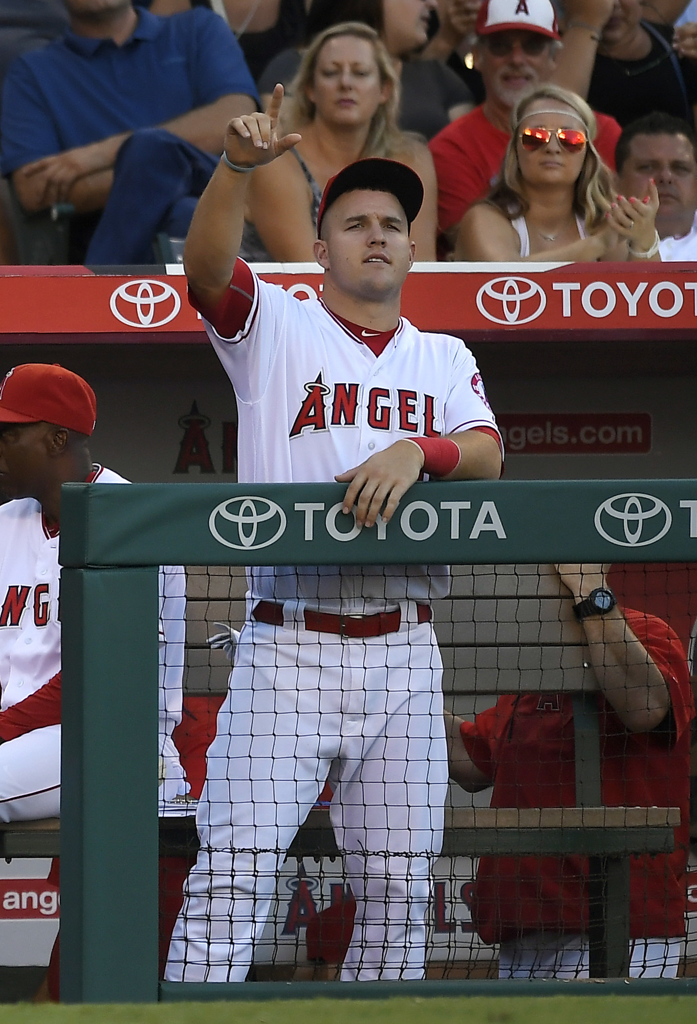 Los Angeles Angels' Mike Trout gestures from the dugout toward first base after C.J. Cron hit an RBI single during the eighth inning of a baseball game against the Cincinnati Reds, Wednesday, Aug. 31, 2016, in Anaheim, Calif. (AP Photo/Mark J. Terrill)