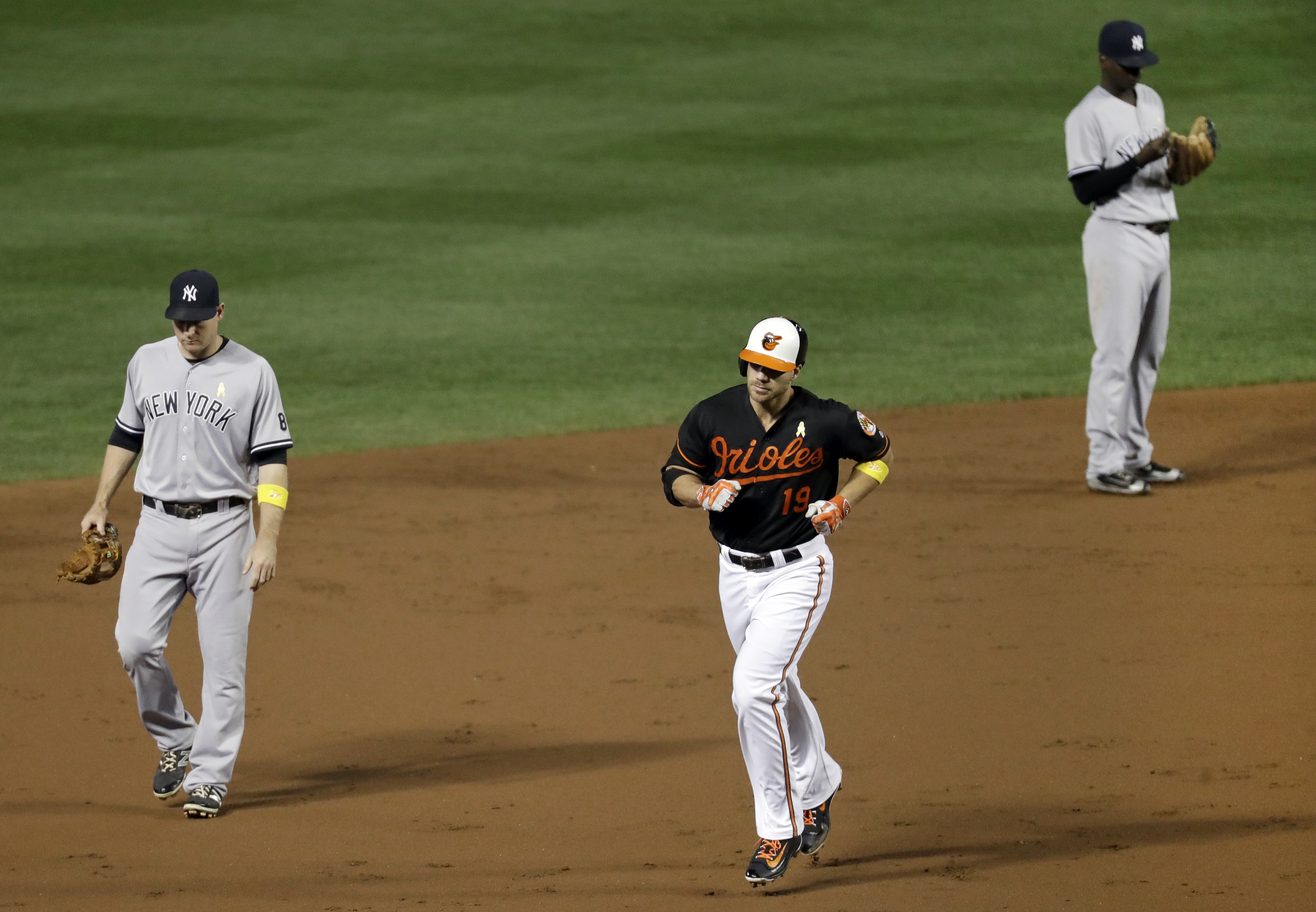 Baltimore Orioles' Chris Davis, center, rounds the bases past New York Yankees third baseman Chase Headley, left, and shortstop Didi Gregorius after hitting a two-run home run during the second inning of a baseball game in Baltimore, Friday, Sept. 2, 2016