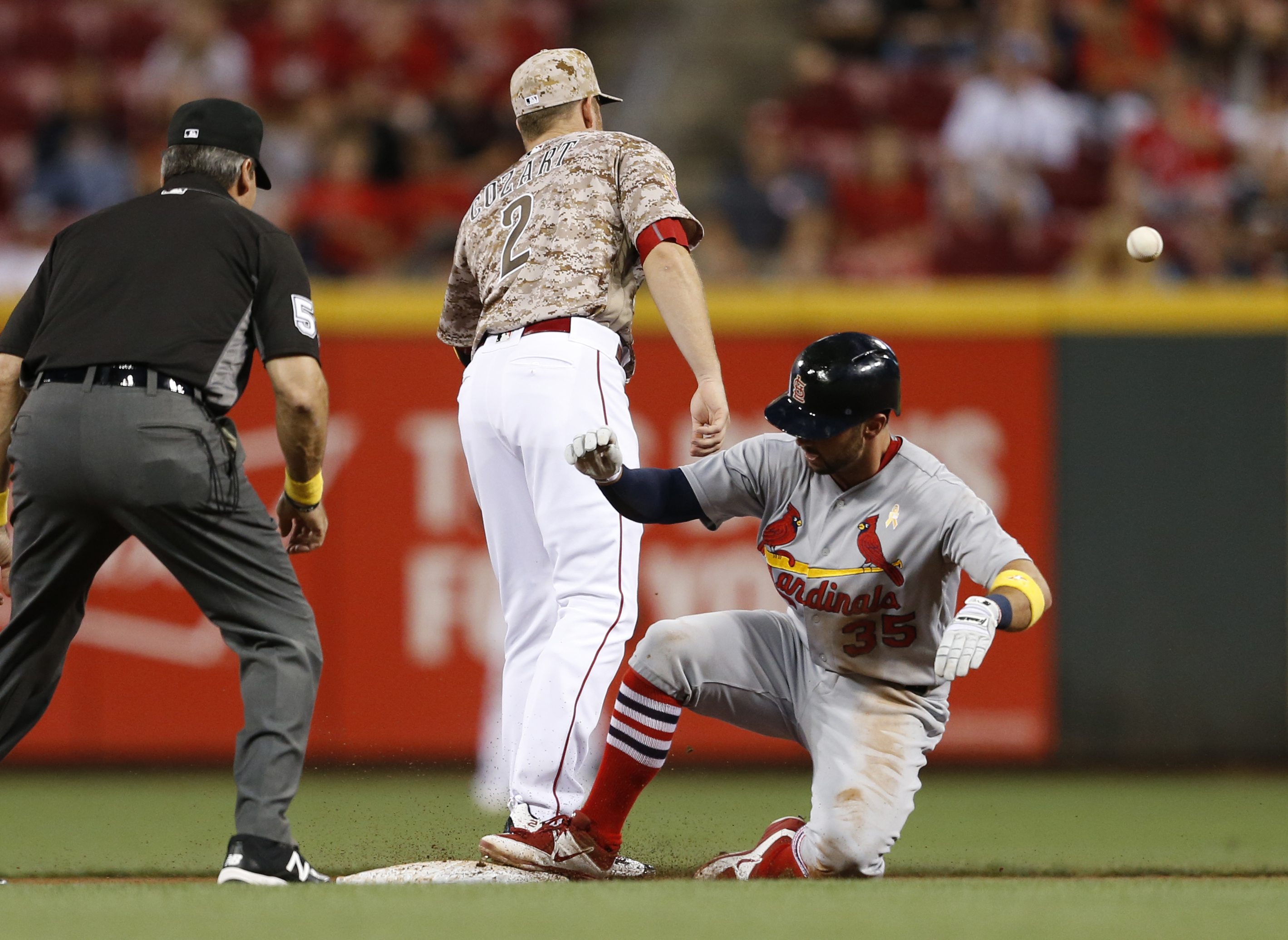 St. Louis Cardinals' Greg Garcia, right, slides into second base with a double as Cincinnati Reds shortstop Zack Cozart (2) waits for the throw during the fifth inning of a baseball game Friday, Sept. 2, 2016, in Cincinnati. (AP Photo/Gary Landers)