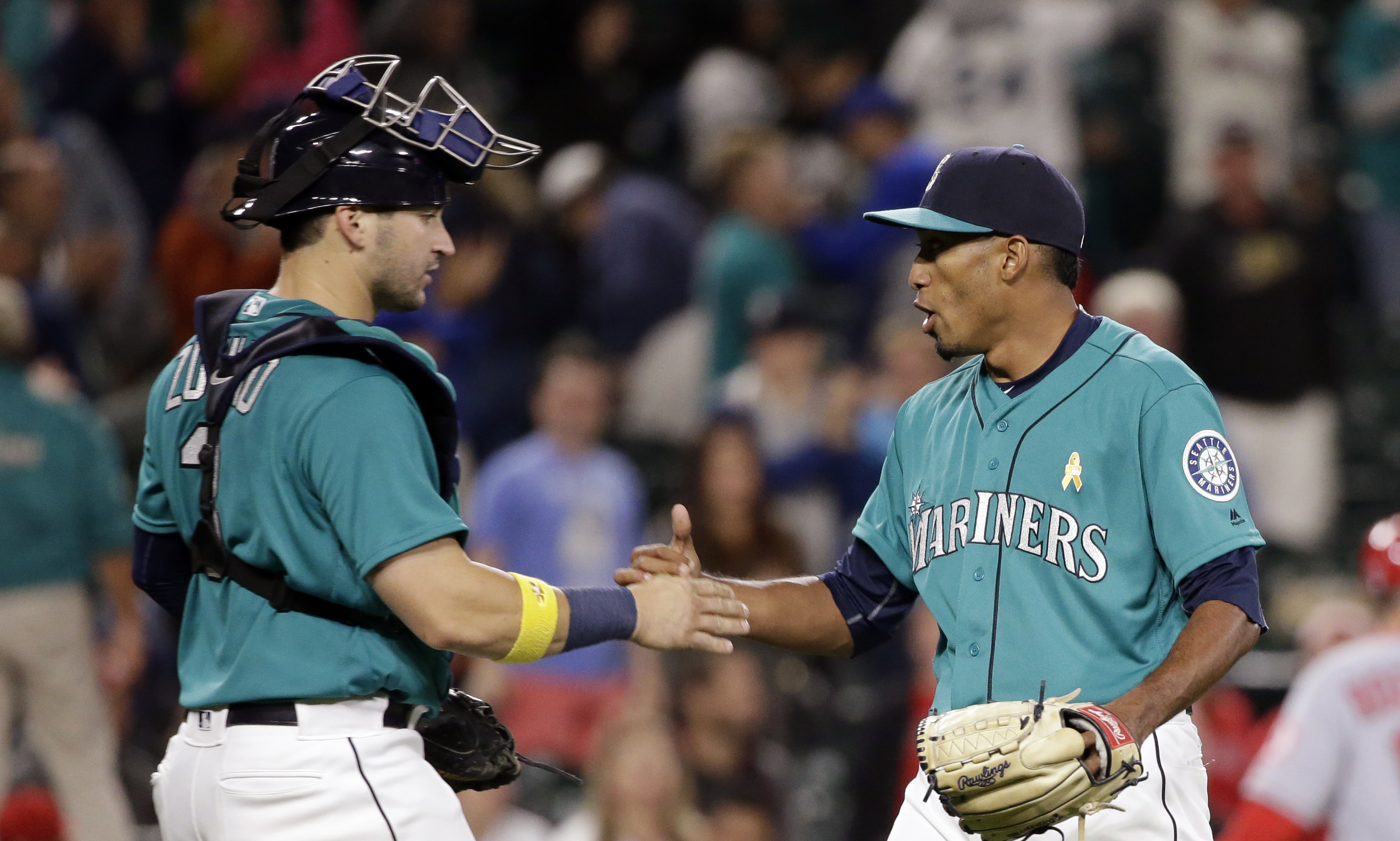 Seattle Mariners catcher Mike Zunino, left, shares congratulations with closing pitcher Edwin Diaz after the Mariners defeated the Los Angeles Angels 11-8 in a baseball game Friday, Sept. 2, 2016, in Seattle. (AP Photo/Elaine Thompson)