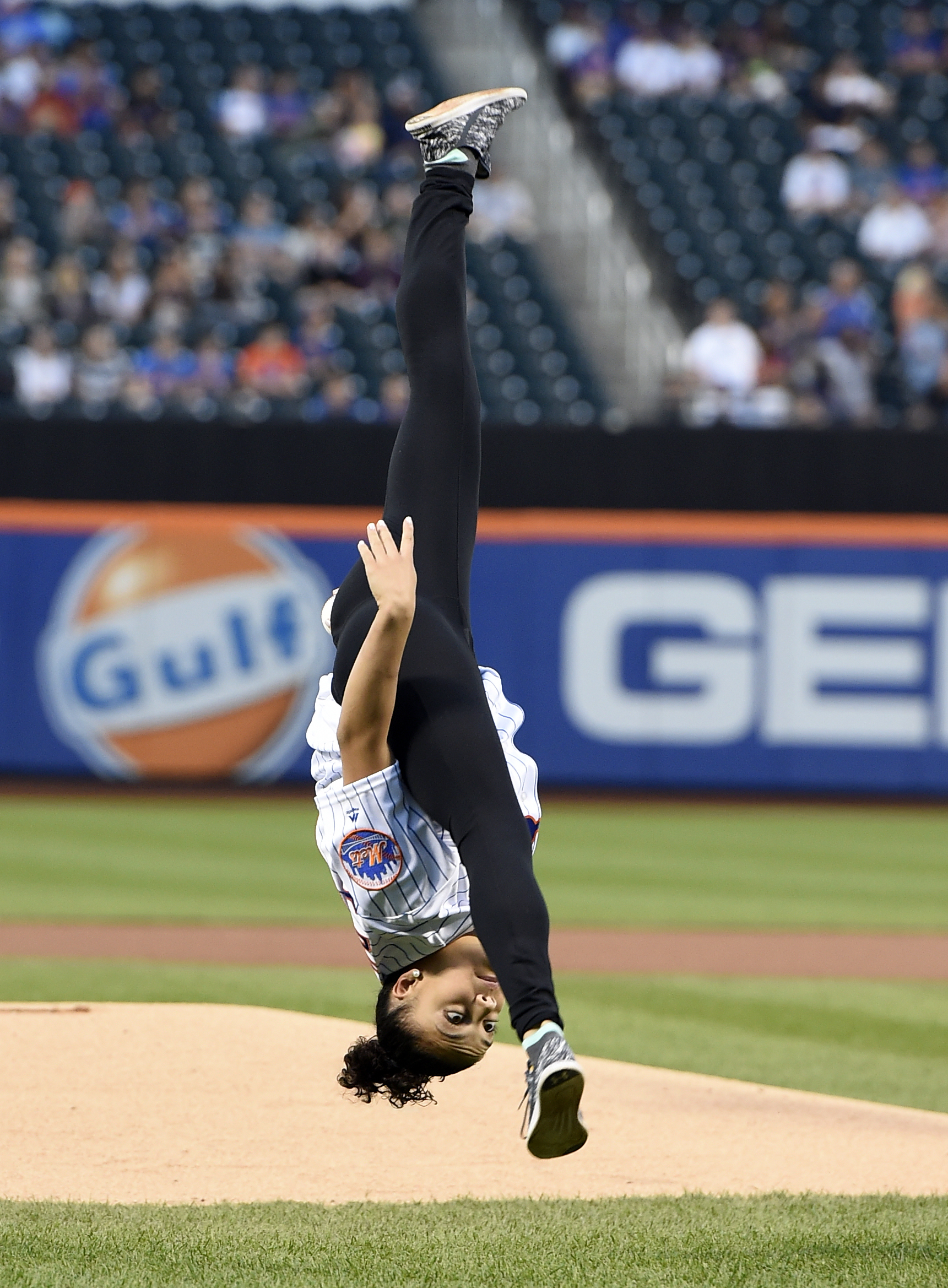 Olympic gold medalist Laurie Hernandez performs flips from the mound before throwing out the ceremonial first pitch before the baseball game between the New York Mets and the Washington Nationals, Saturday, Sept. 3, 2016, in New York. (AP Photo/Kathy Kmon