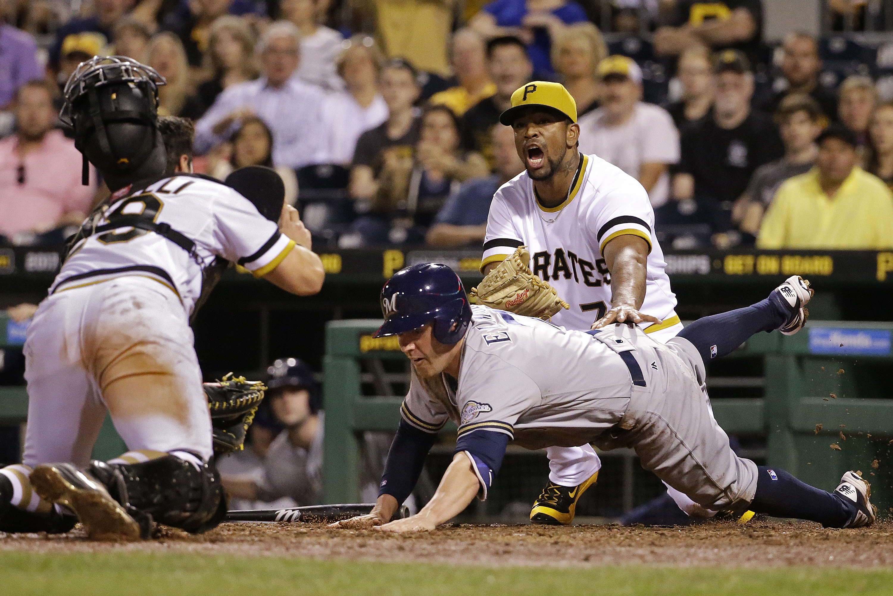 Milwaukee Brewers' Jake Elmore, center, dives back to touch home plate after sliding past it as Pittsburgh Pirates catcher Francisco Cervelli, left, attempts to make the tag with pitcher Felipe Rivero, rear, during the eighth inning of a baseball game in