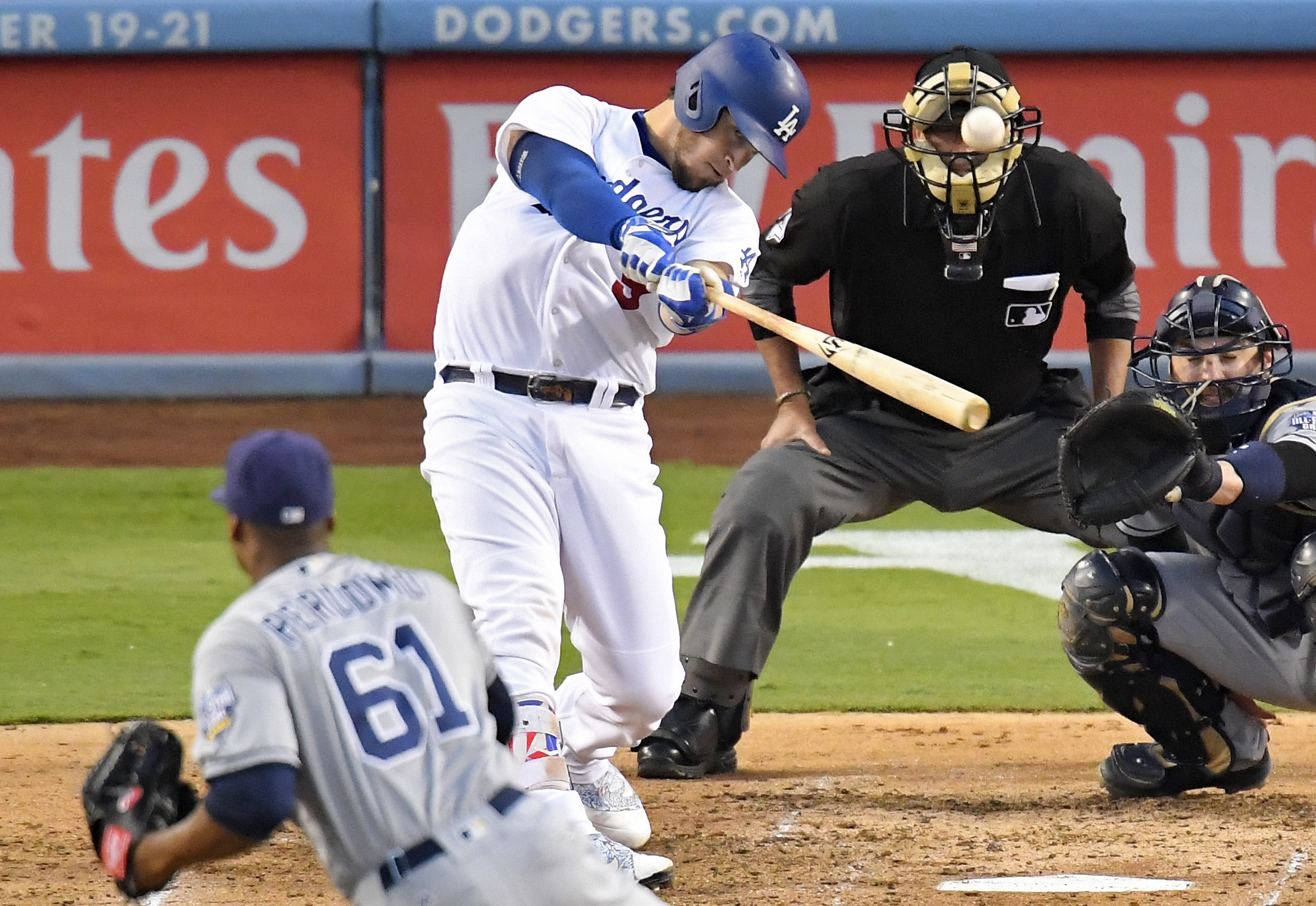 Los Angeles Dodgers' Yasmani Grandal, second from left, hits a three-run home run as San Diego Padres relief pitcher Luis Perdomo, left, and catcher Derek Norris, right, watch along with home plate umpire John Hirschbeck during the fourth inning of a base