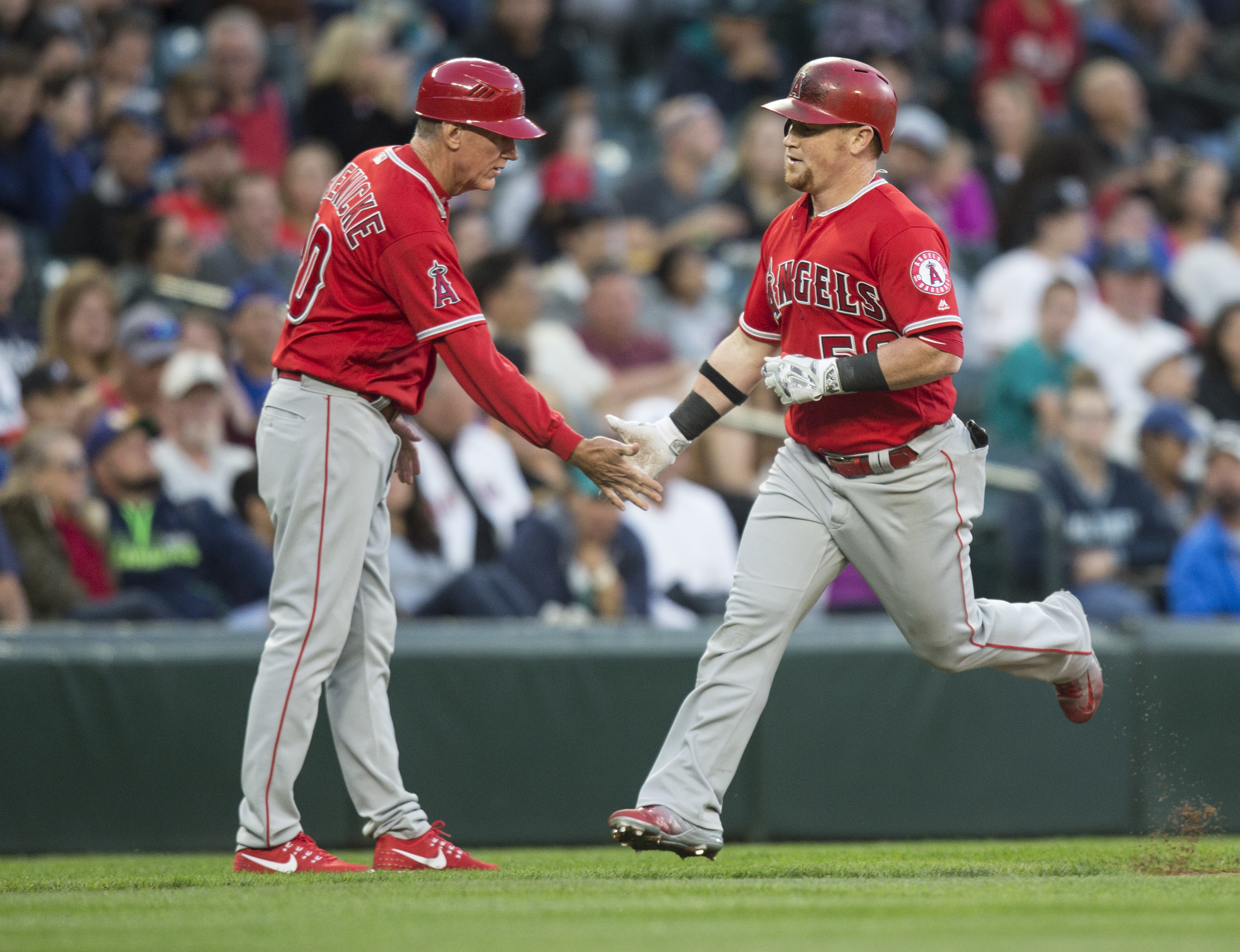 Los Angeles Angels' Kole Calhoun is congratulated by third base coach Rick Roenicke after hitting a solo home run off of Seattle Mariners relief pitcher Pat Venditte during the third inning of a baseball game, Saturday, Sept. 3, 2016, in Seattle. It was C
