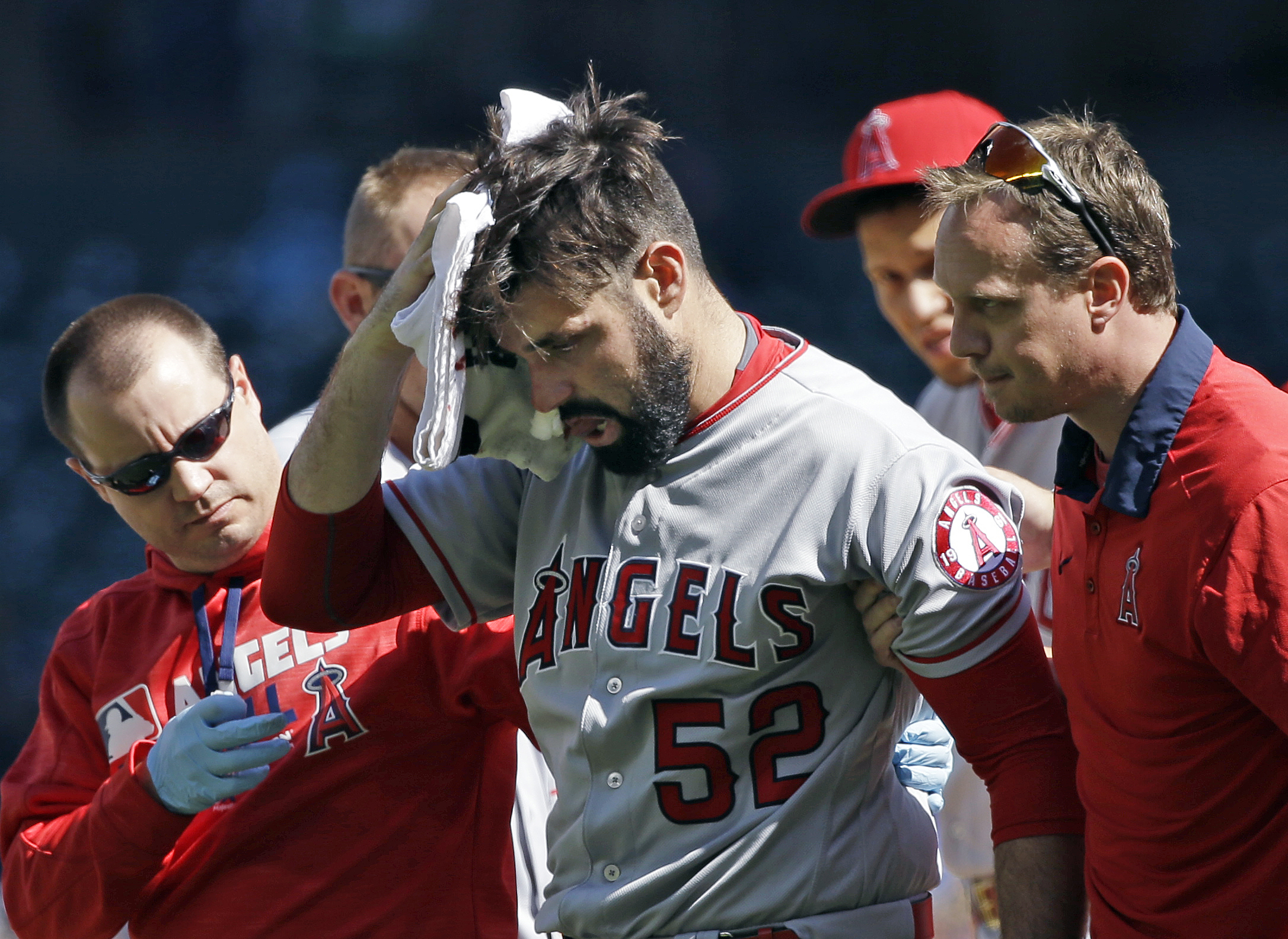 Los Angeles Angels starting pitcher Matt Shoemaker is assisted off the field after being hit by a line drive from Seattle Mariners' Kyle Seager in the second inning of a baseball game, Sunday, Sept. 4, 2016, in Seattle. (AP Photo/Elaine Thompson)