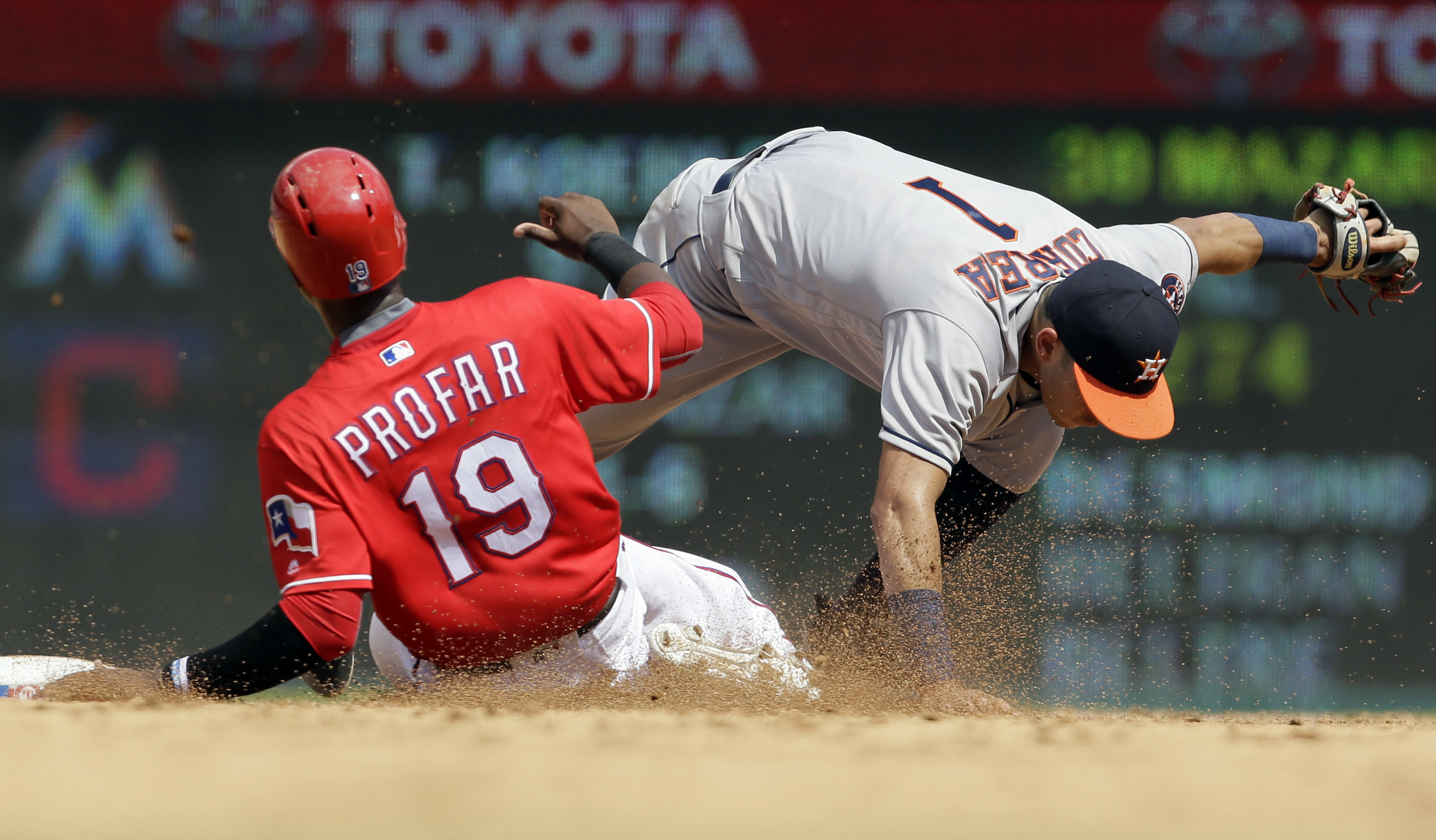 Houston Astros shortstop Carlos Correa (1) holds onto the ball as Texas Rangers' Jurickson Profar (19) slides into second base on a force-out during the third inning of a baseball game in Arlington, Texas, Sunday, Sept. 4, 2016. Rangers' Nomar Mazara was