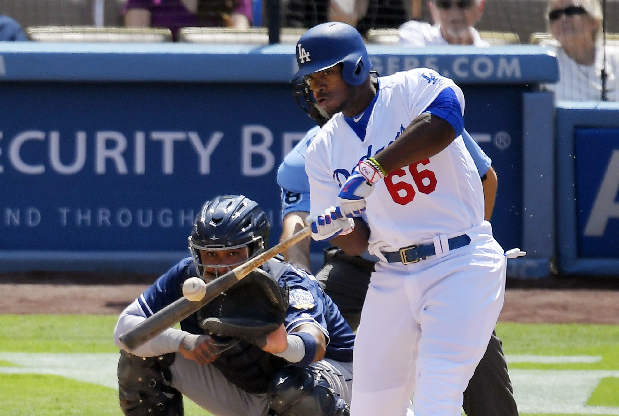 Los Angeles Dodgers' Yasiel Puig, right, hits a three-run home run as San Diego Padres catcher Hector Sanchez watches during the third inning of a baseball game, Sunday, Sept. 4, 2016, in Los Angeles. (AP Photo/Mark J. Terrill)